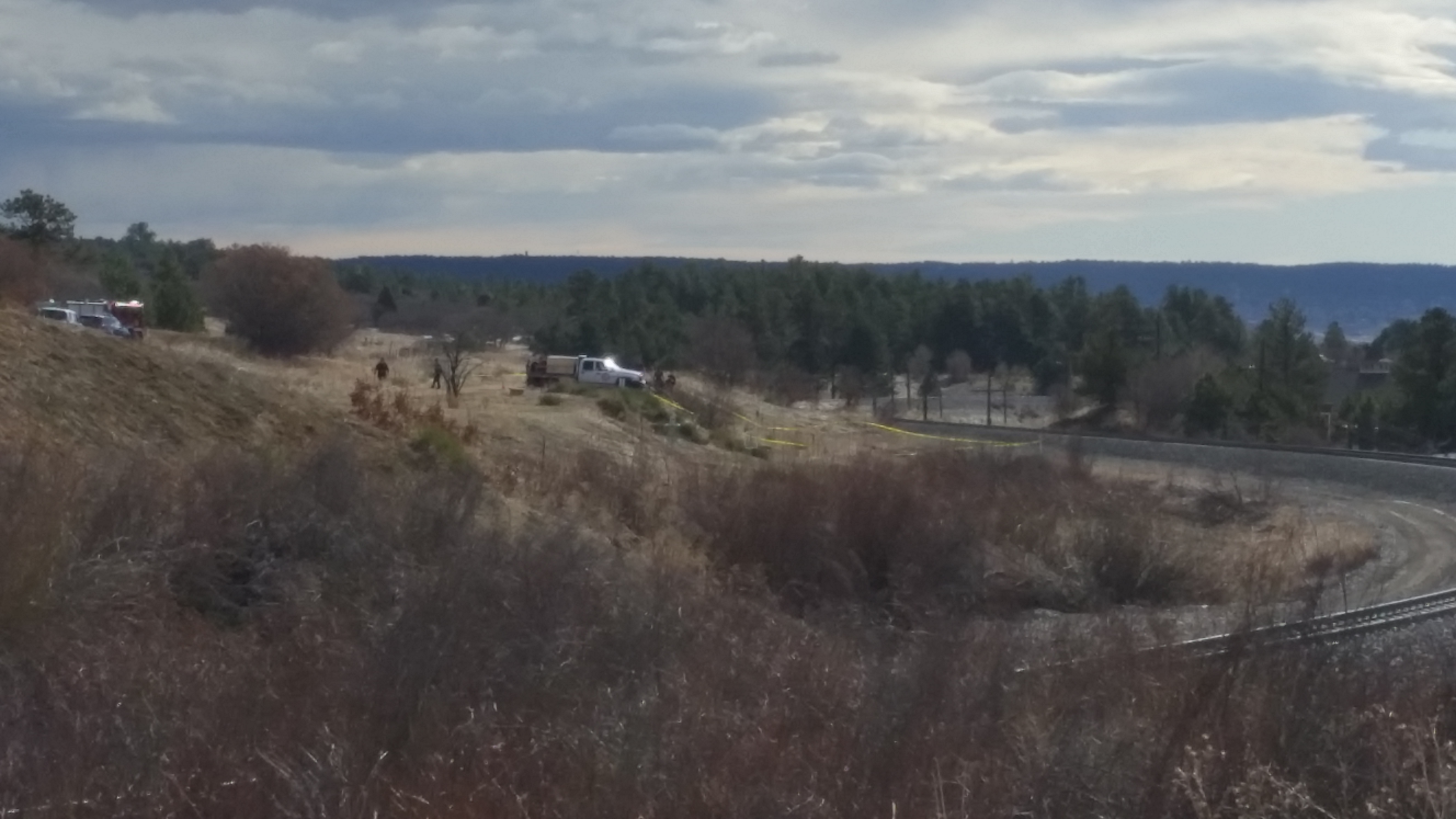 The scene of a plane crash near Palmer Lake Wednesday morning. The burned-out frame of the plane can be seen in front of the white truck. / Tyler Barton - FOX21 News