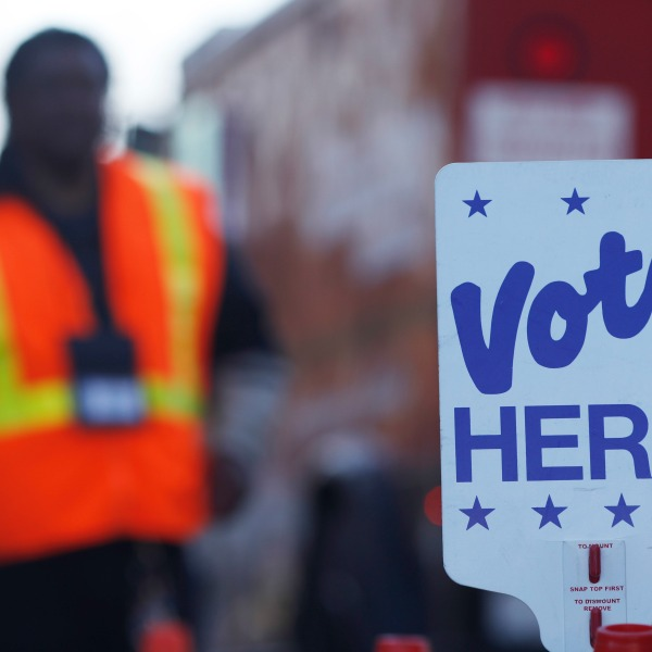With the sign for ballot drop off in the foreground, election judge Ed Wingfield waits for motorists drop off ballots outside the Denver Election Commission headquarters on Tuesday, Nov. 8, 2016, in downtown Denver. (AP Photo/David Zalubowski)