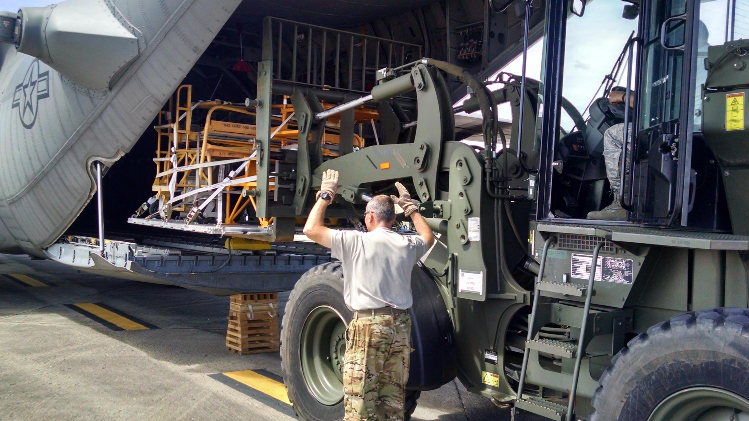 A 302nd Airlift Wing loadmaster guides a cargo load onto an Air Force Reserve Command C-130 Hercules aircraft Sept. 25, at the San Juan Interna_319582