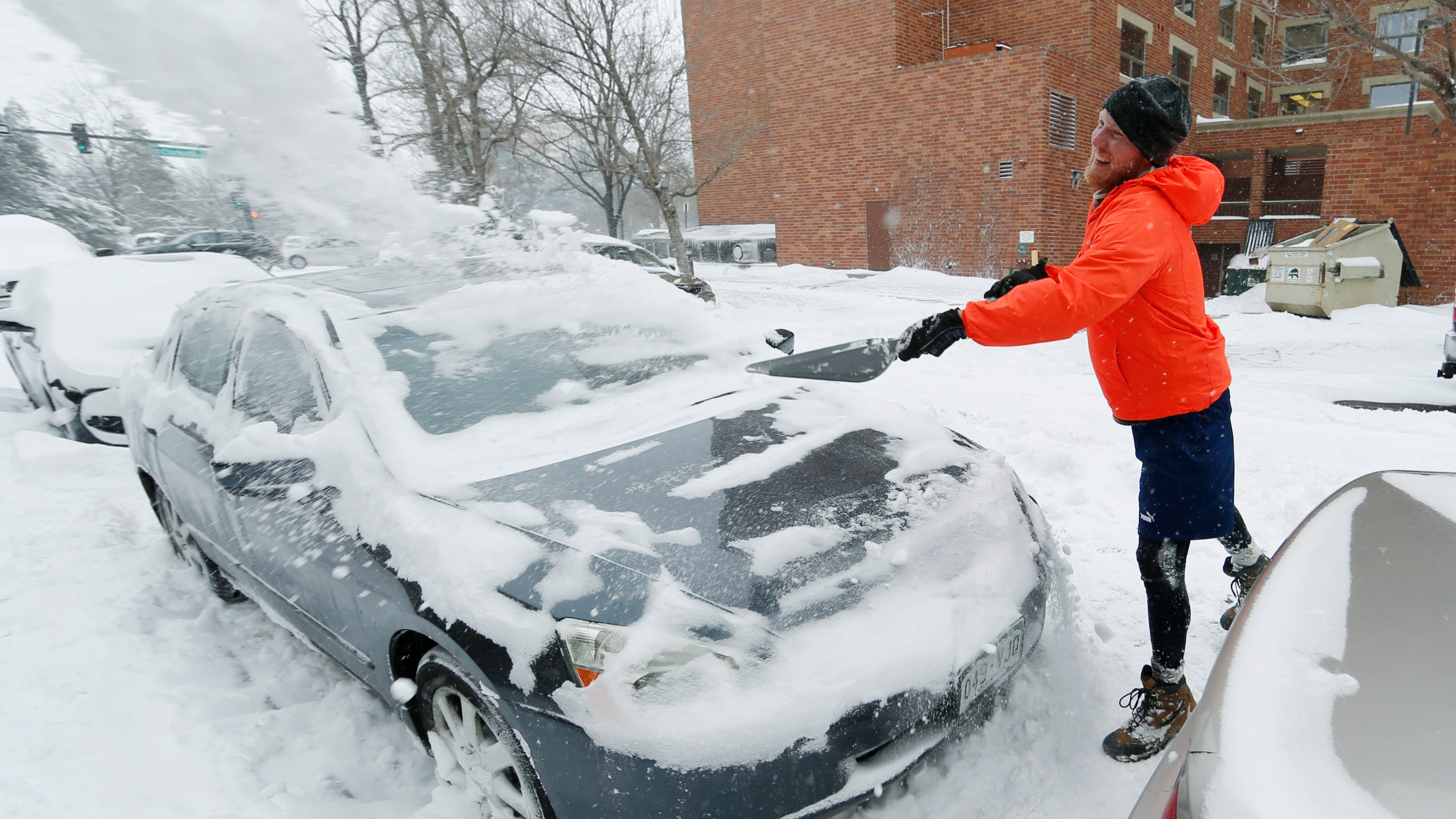 John Malsbary launches a shovelful of snow over his car as he tries to dig the vehicle out of a curbside parking spot as high winds drive granu_334494