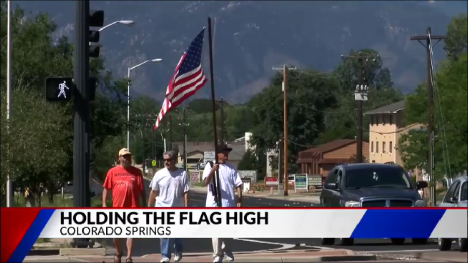 Criss Seal carries the American flag at the intersection of Academy Boulevard and Galley Road on September 11, 2018. FOX21 News file photo