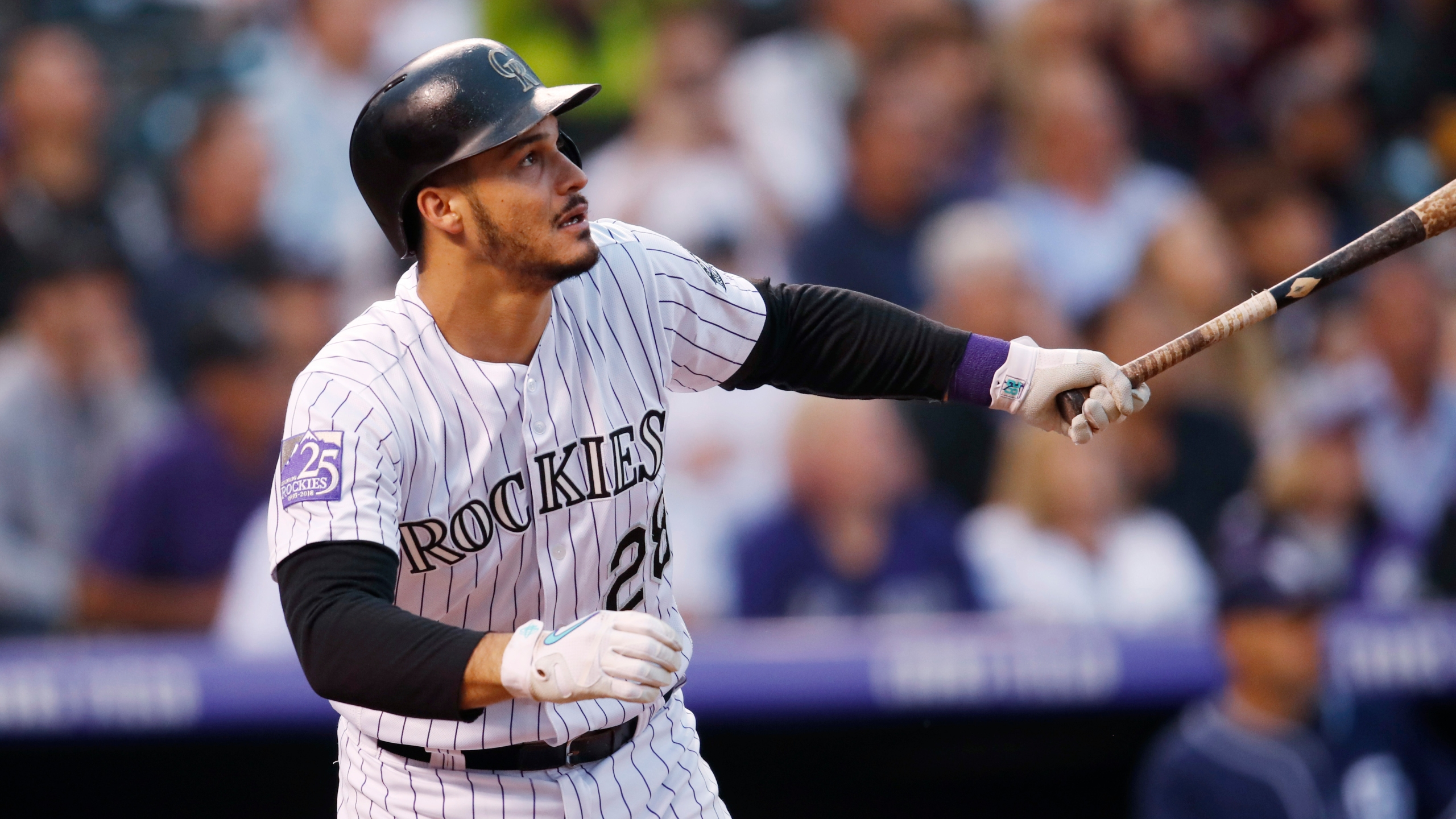 Colorado Rockies' Nolan Arenado follows the flight of his RBI-double off San Diego Padres relief pitcher Robbie Erlin in the third inning of a basebal