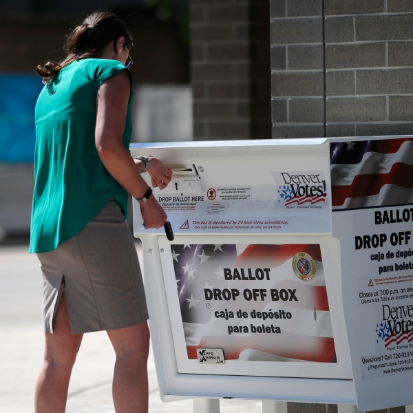 A voter drops her primary election ballot in a collection box outside the Denver Elections Division headquarters early Tuesday, June 26, 2018, in Denv