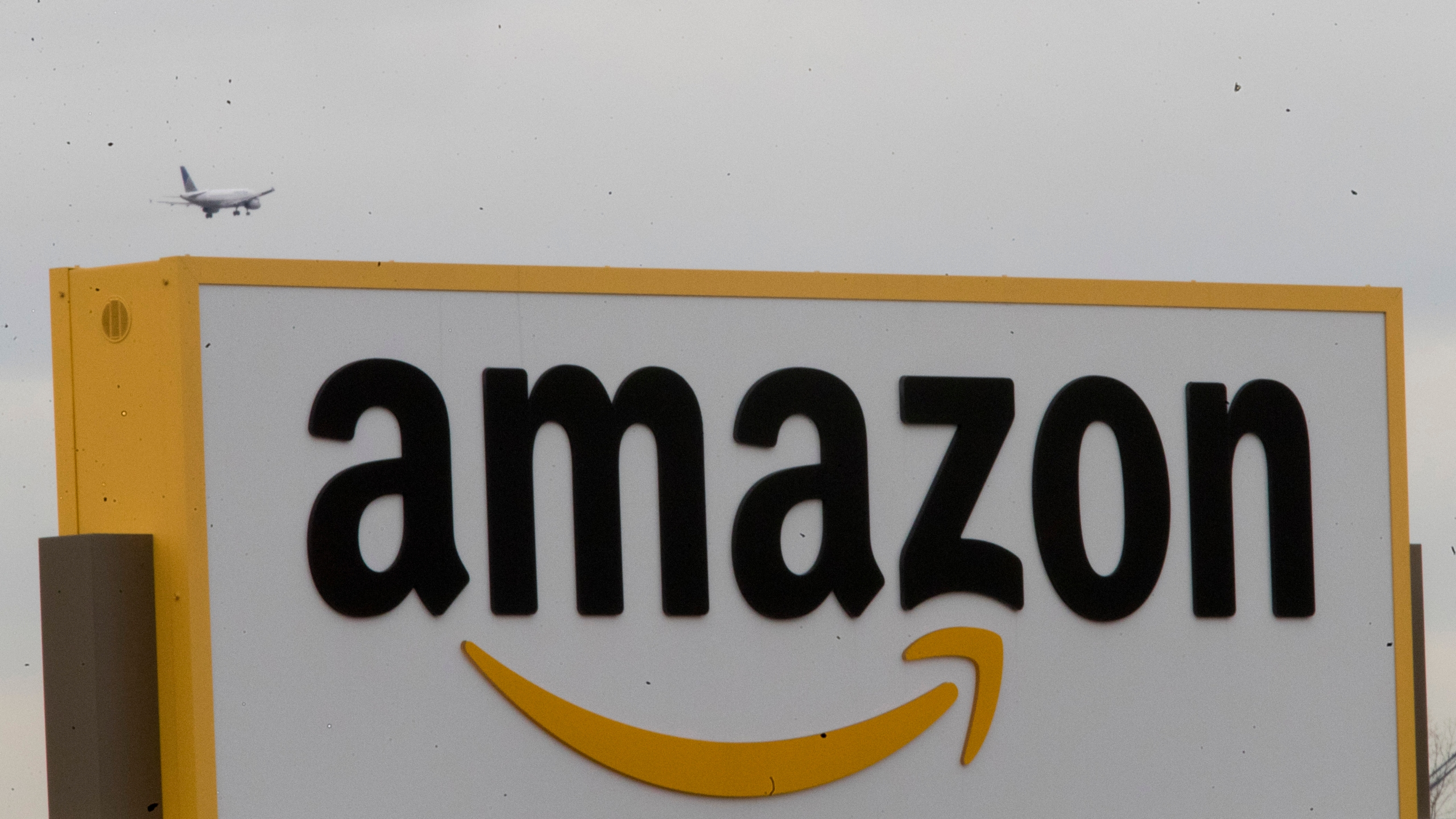 In this Wednesday, Dec. 5, 2018, an airplane flies over the Amazon sign at the Amazon fulfillment center on Staten Island borough of New York. AP Pho