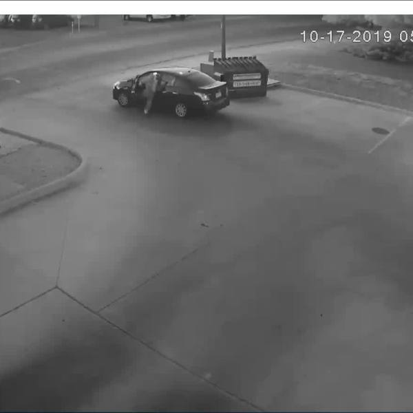 Still from video shows a person dumping a suitcase containing a woman's body into a dumpster at a Pueblo car wash Thursday morning. / Pueblo Police Department