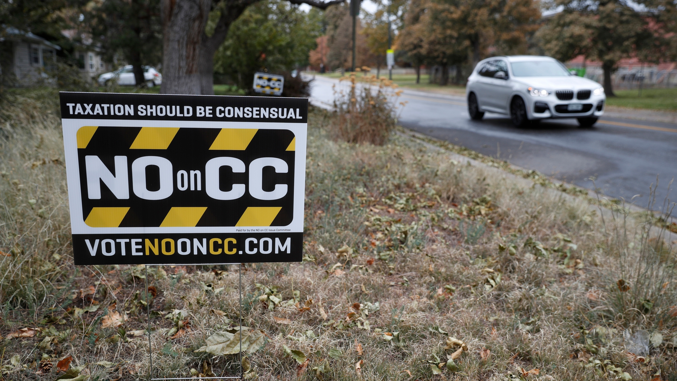 In this Friday, Oct. 18, 2019, photograph, a vehicle passes by a lawn sign calling for voters to cast ballots against a measure to dismantle part of Colorado's state tax laws on election day Tuesday, Nov. 5. (AP Photo/David Zalubowski)