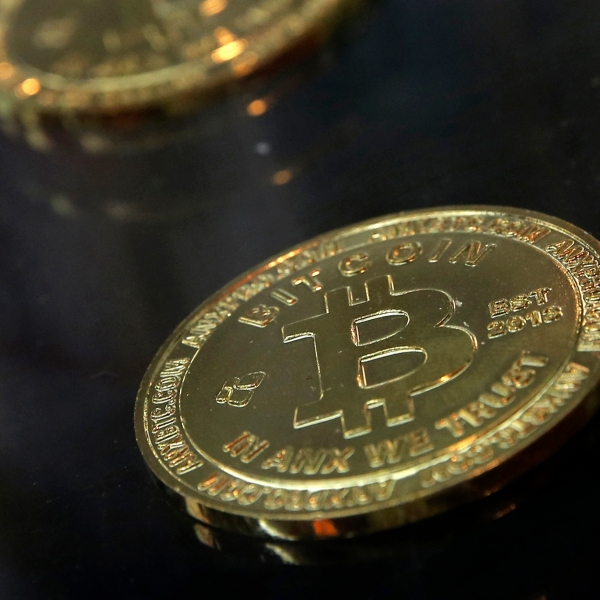 FILE- In this Dec. 8, 2017, file photo, coins are displayed next to a Bitcoin ATM in Hong Kong. (AP Photo/Kin Cheung, File)