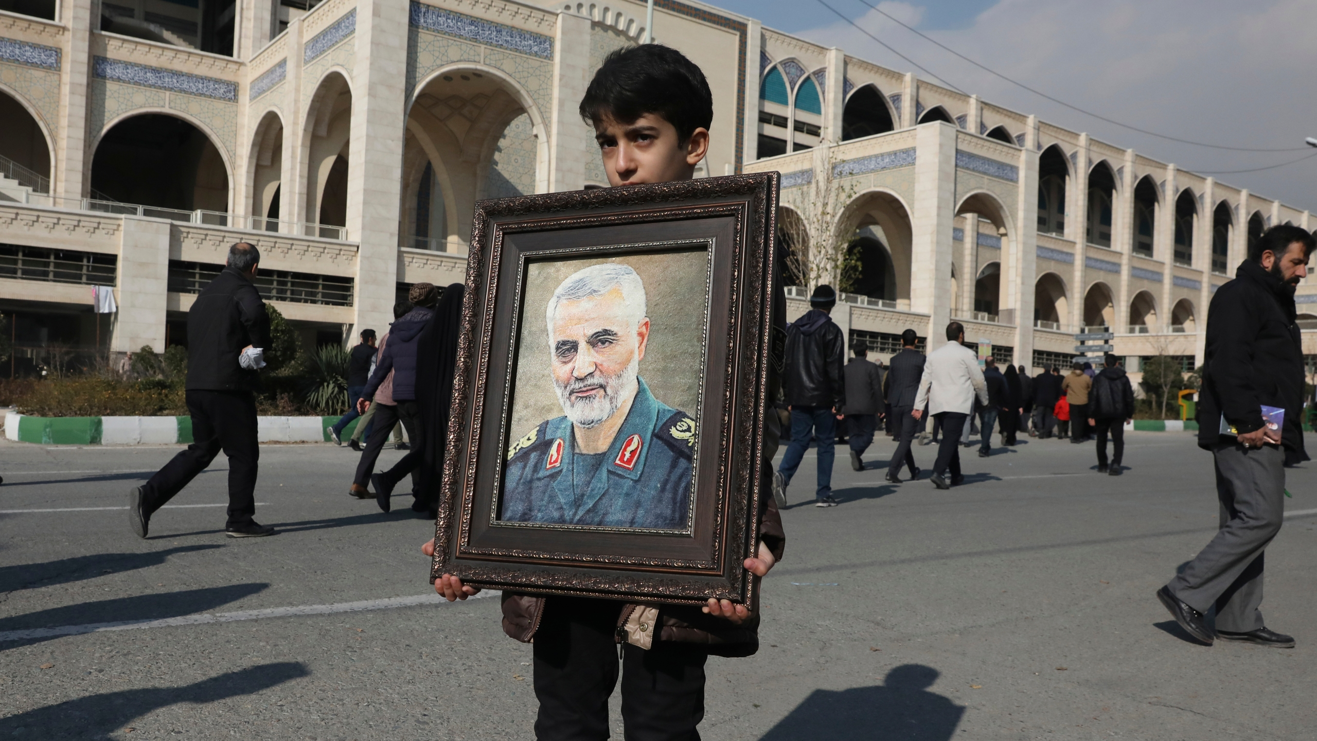 """A boy carries a portrait of Iranian Revolutionary Guard Gen. Qassem Soleimani, who was killed in the U.S. airstrike in Iraq, prior to the Friday prayers in Tehran, Iran, Friday Jan. 3, 2020. Iran has vowed """"harsh retaliation"""" for the U.S. airstrike near Baghdad's airport that killed Tehran's top general and the architect of its interventions across the Middle East, as tensions soared in the wake of the targeted killing. (AP Photo/Vahid Salemi)"""