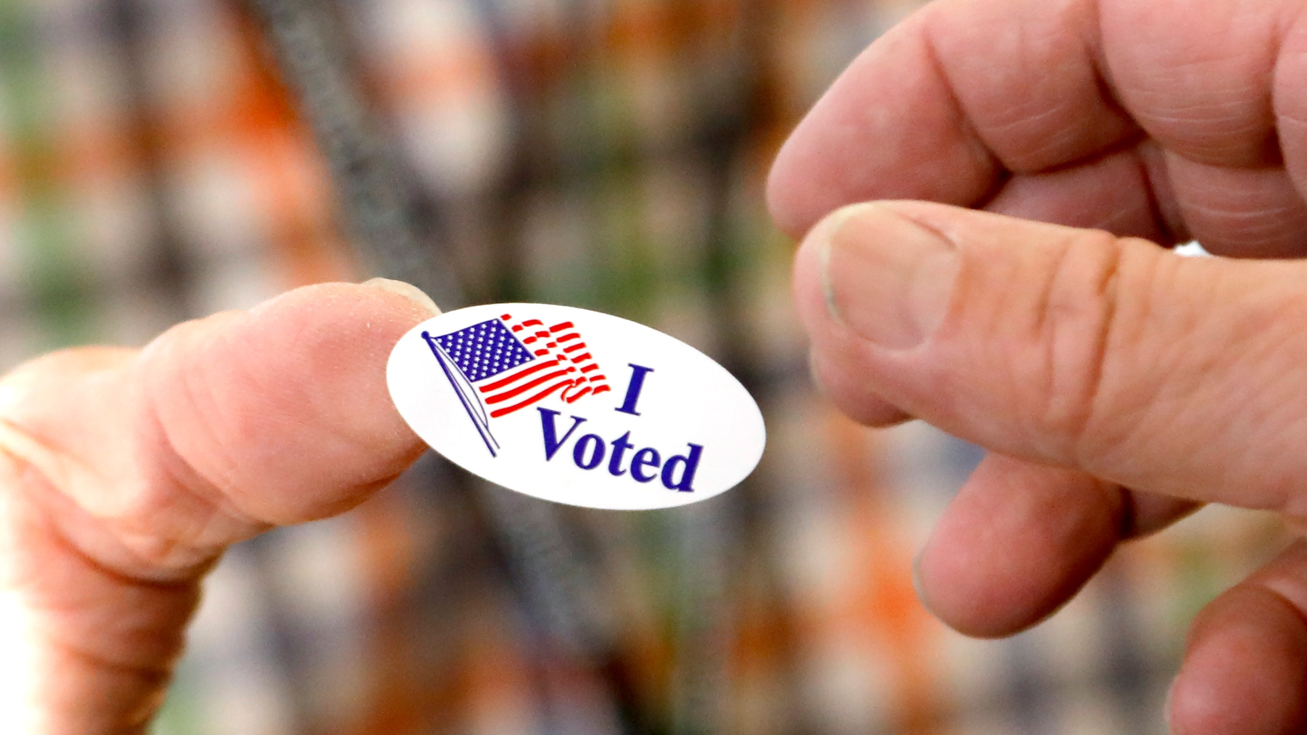 """FILE - In this Tuesday, Nov. 5, 2019 file photo, a poll worker offers a voter an """"I Voted"""" sticker after casting a ballot in Ridgeland, Miss. (AP Photo/Rogelio V. Solis)"""