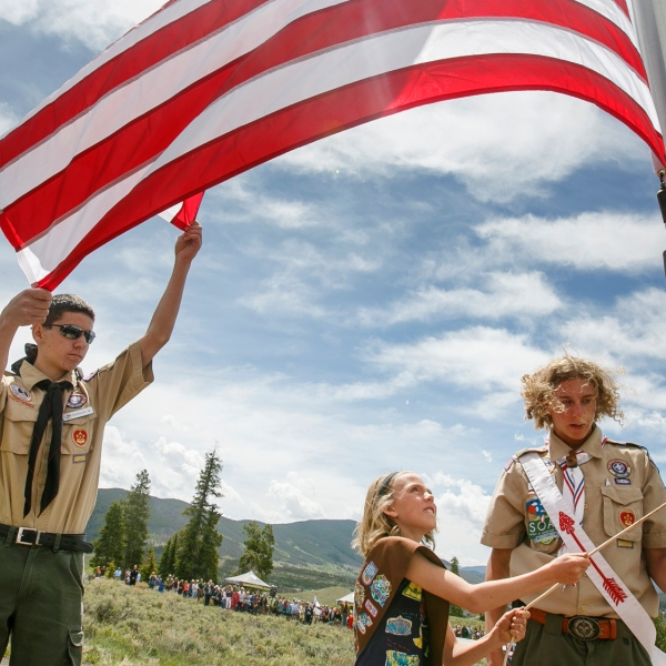 In a Monday, May 28, 2018 photo, Summit County Boy Scout and Cub Scout members, Morgan McGuire, from left, Lydia Ashley, and Jeremiah Vaille raise a new flag during a Memorial Day ceremony at the Dillon Cemetery in Dillon, Colo. (Hugh Carey/Summit Daily News via AP)