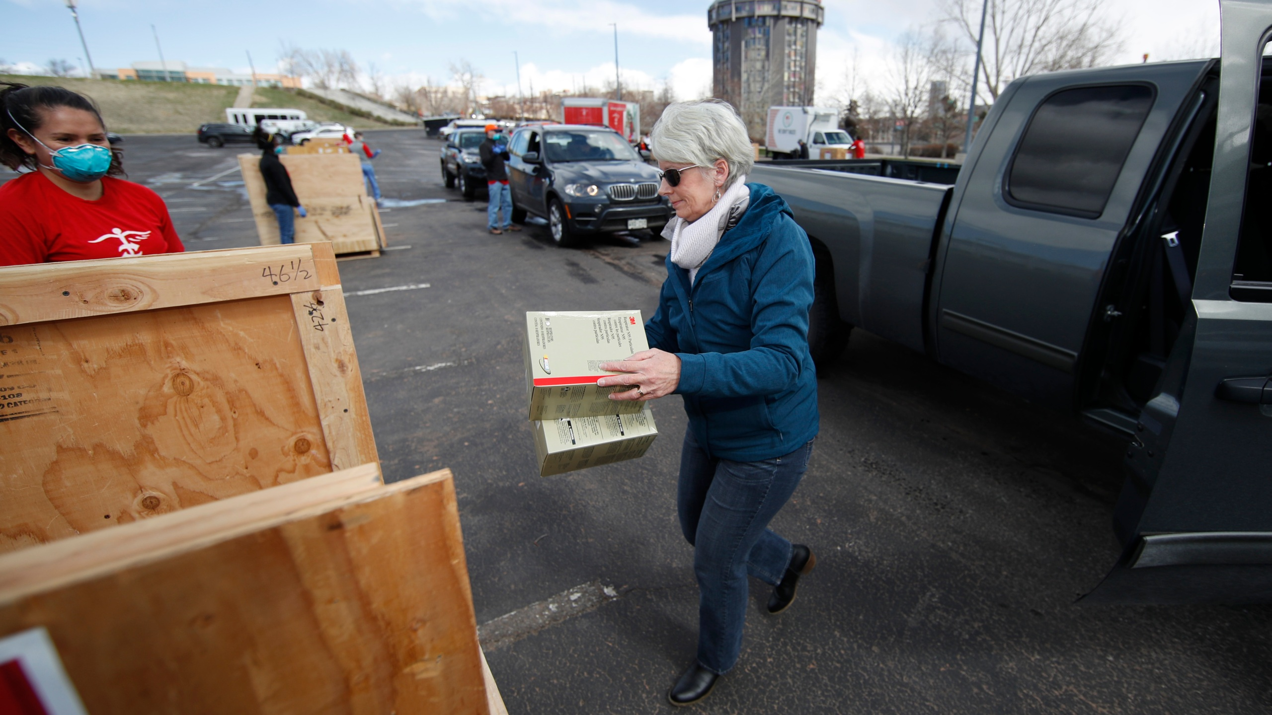 A woman carries protective masks to a bin as medical supplies are donated as part of an effort staged by two state lawmakers, Project C.U.R.E., Colorado Concern and the Denver Broncos to battle the spread of coronavirus Sunday, March 22, 2020, in Denver. (AP Photo/David Zalubowski)