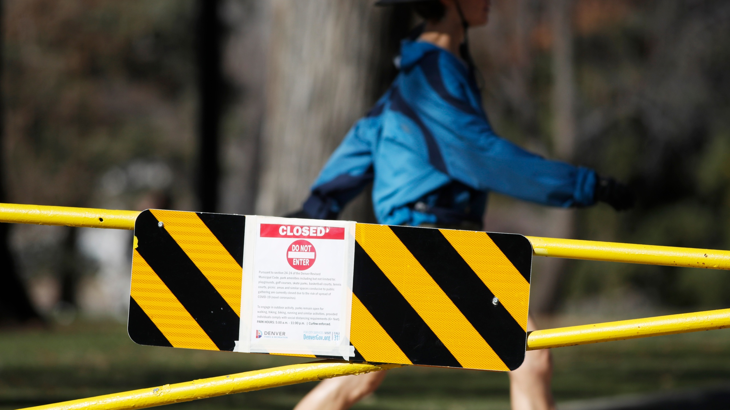 A walker passes by the gate bearing a sign that Washington Park is closed to any group activities as a mayoral edict goes into effect to close city playgrounds, golf courses, skate parks, basketball and tennis courts until Friday, April 10, to reduce the spread of the new coronavirus Monday, March 24, 2020, in Denver.(AP Photo/David Zalubowski)