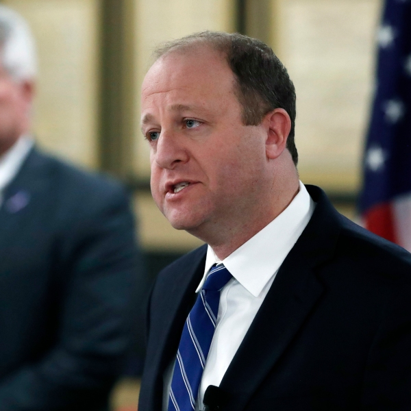 Colorado Gov. Jared Polis announces during a news conference a statewide stay-at-home order to reduce the spread of the new coronavirus Wednesday, March 25, 2020, in Centennial, Colo. The order goes into effect Thursday, March 26, and is in place through Thursday, April 11. (AP Photo/David Zalubowski)