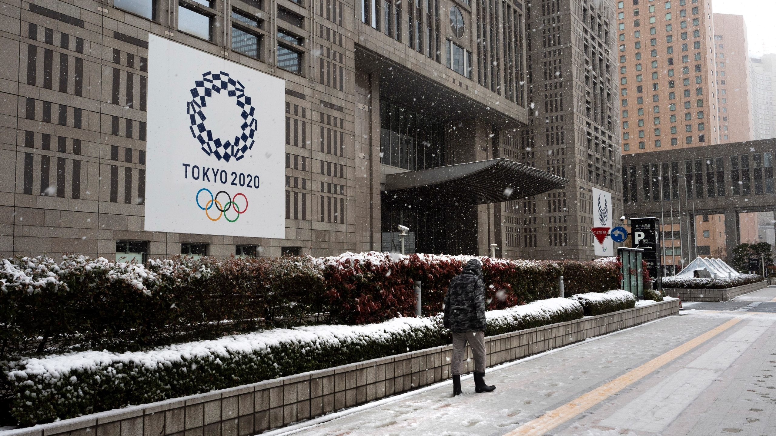 A man walks along a snow-covered sidewalk past a banner promoting the Tokyo 2020 Olympics Sunday, March 29, 2020, in Tokyo. (AP Photo/Jae C. Hong)