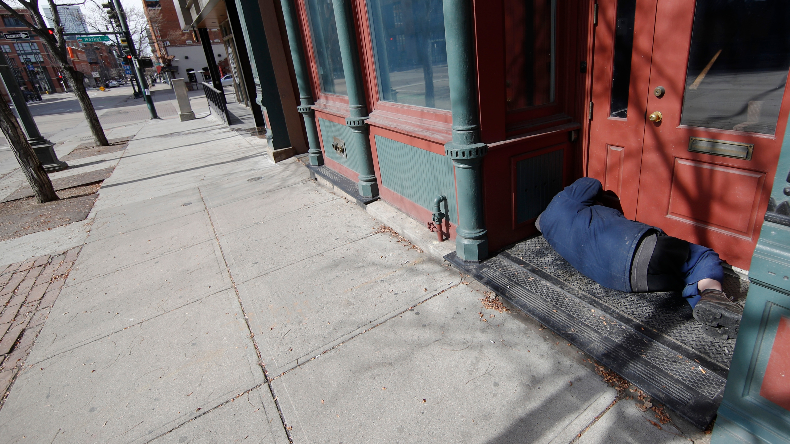 A homeless man sleeps in the doorway of an empty storefront as residents deal with the spread of coronavirus Saturday, March 21, 2020, in Denver.(AP Photo/David Zalubowski)