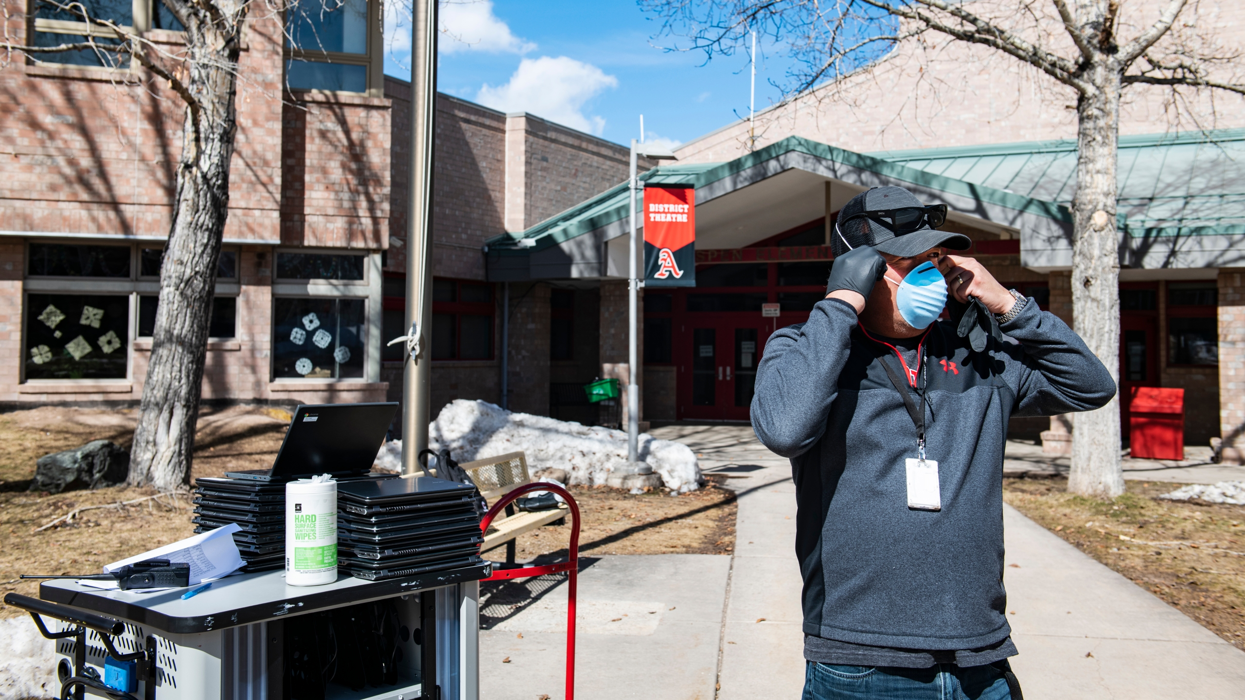 Aspen Elementary School technology integrator Dave Fuentes puts his mask on while preparing and distributing student's laptops outside of the school on Wednesday, April 1, 2020. (Kelsey Brunner/The Aspen Times via AP)