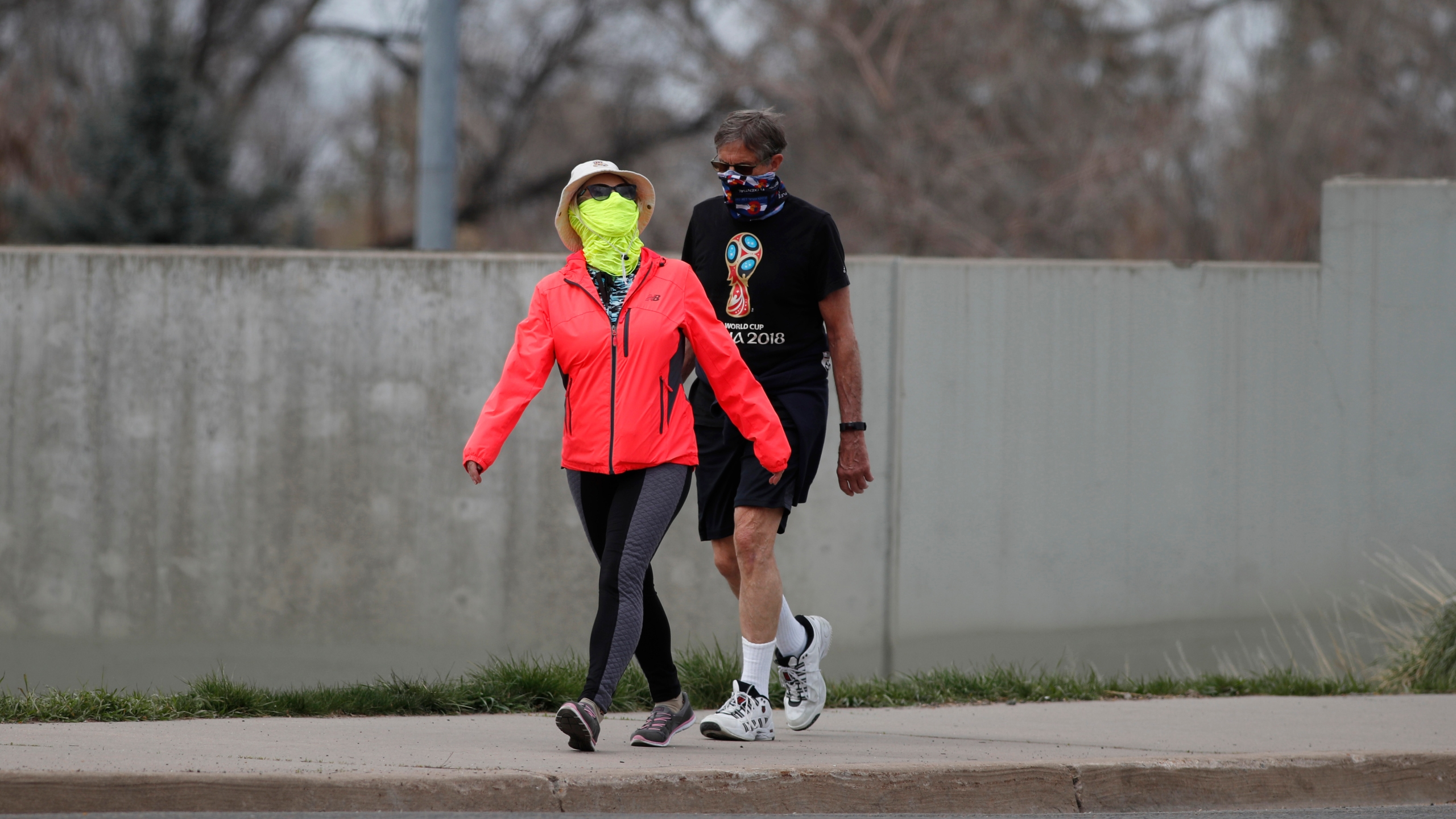 Pedestrians wear masks to comply with a request by Colorado Gov. Jared Polis while they walk along South St. Paul Street as a statewide stay-at-home order remains in effect in an effort to reduce the spread of the new coronavirus, Sunday, April 5, 2020, in Denver. (AP Photo/David Zalubowski)