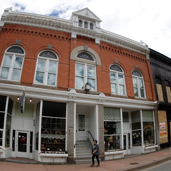 As viewed through a fisheye lens, a lone pedestrian walks along Sixth Street pat shuttered shops closed to help in the effort to stop the spread of the new coronavirus, Wednesday, May 27, 2020, in Georgetown, Colo. (AP Photo/David Zalubowski)