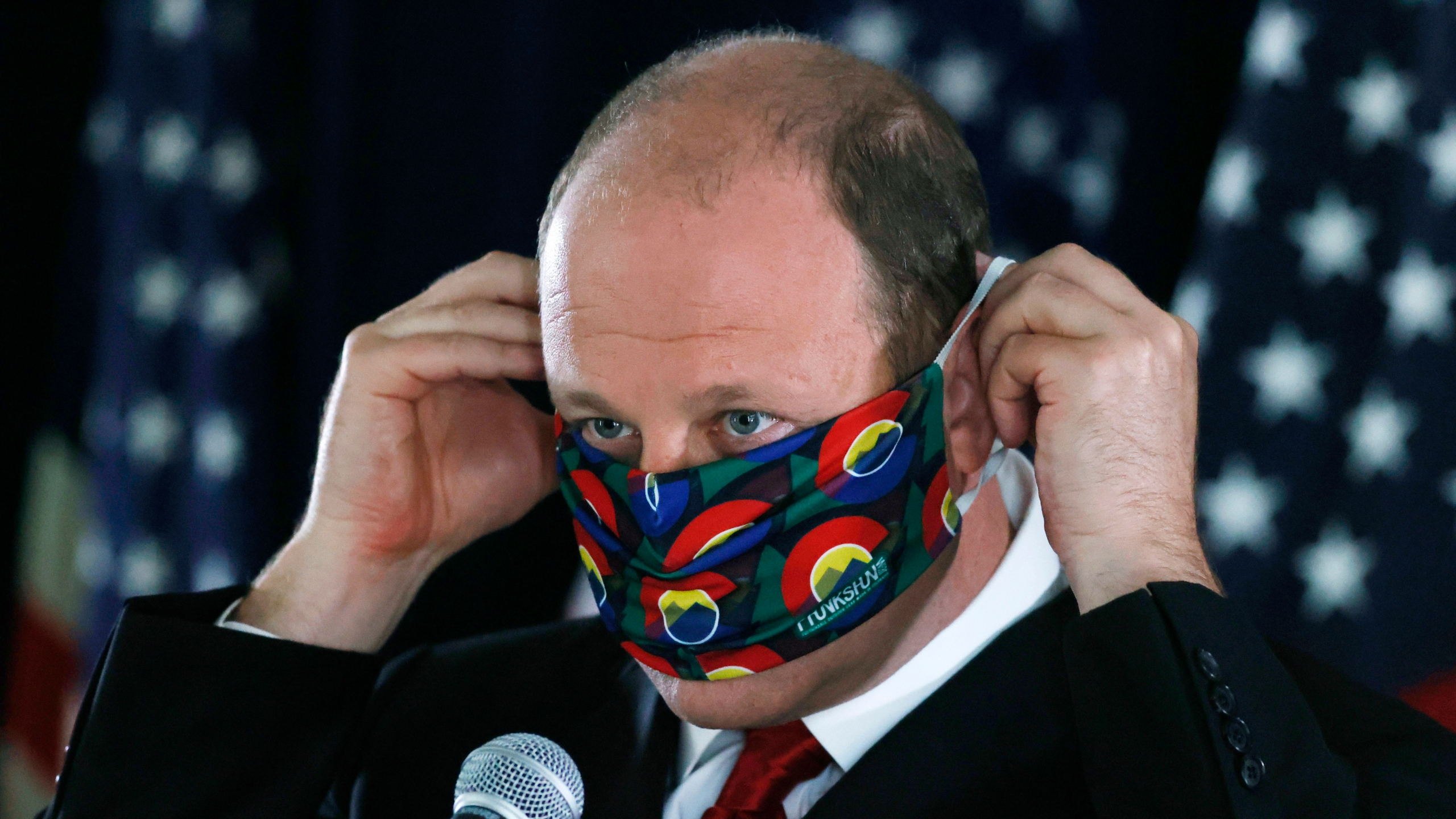FILE—In this Thursday, May 28, 2020, file photograph, Colorado Governor Jared Polis puts on his face mask after a news conference about the state's efforts against the new coronavirus in Denver. (AP Photo/David Zalubowski, File)