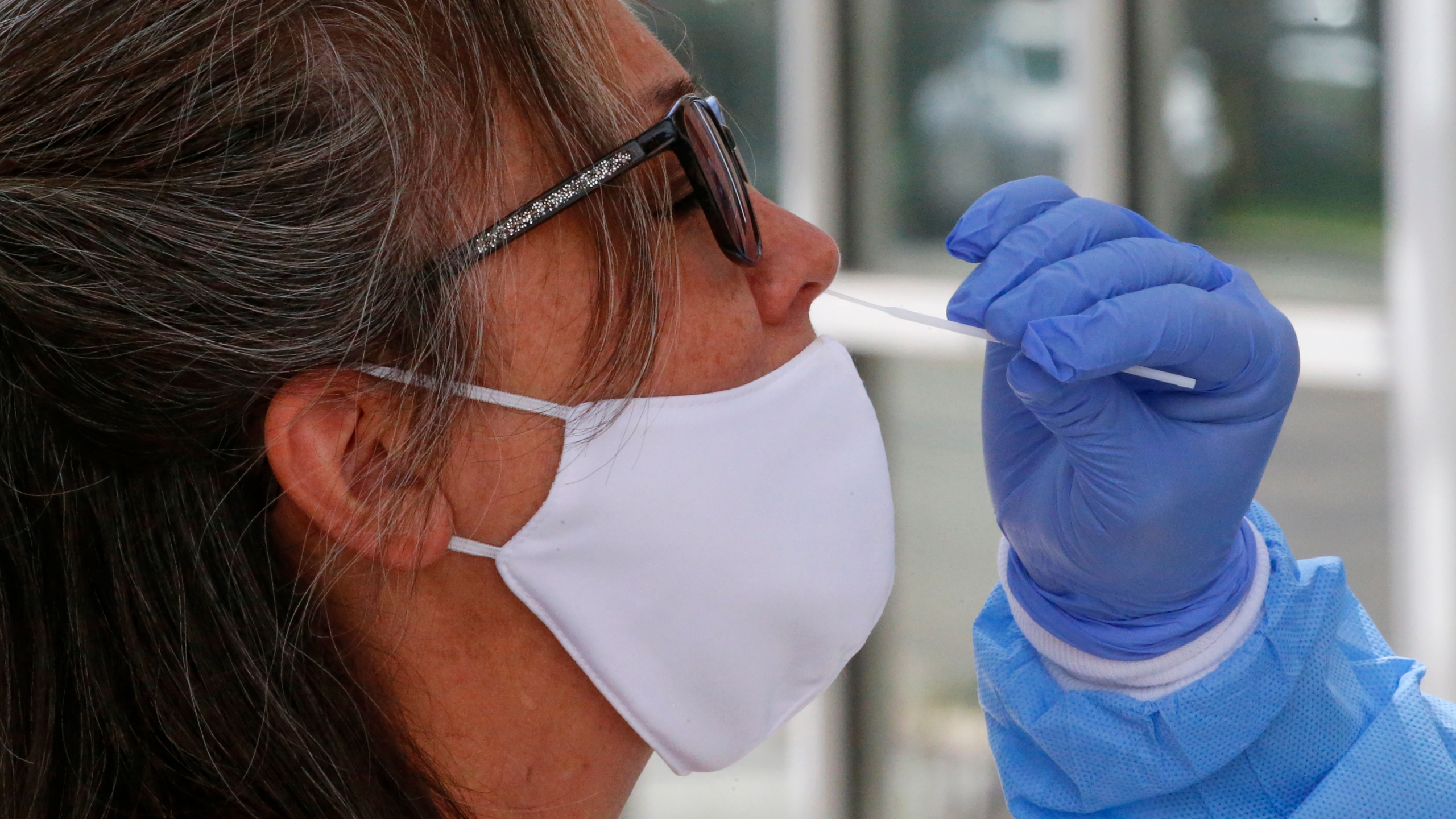 A woman receives a coronavirus test from Salt Lake County Health Department public health nurse Lee Cherie Booth outside the Salt Lake County Health Department Friday, June 12, 2020, in Salt Lake City. (AP Photo/Rick Bowmer)