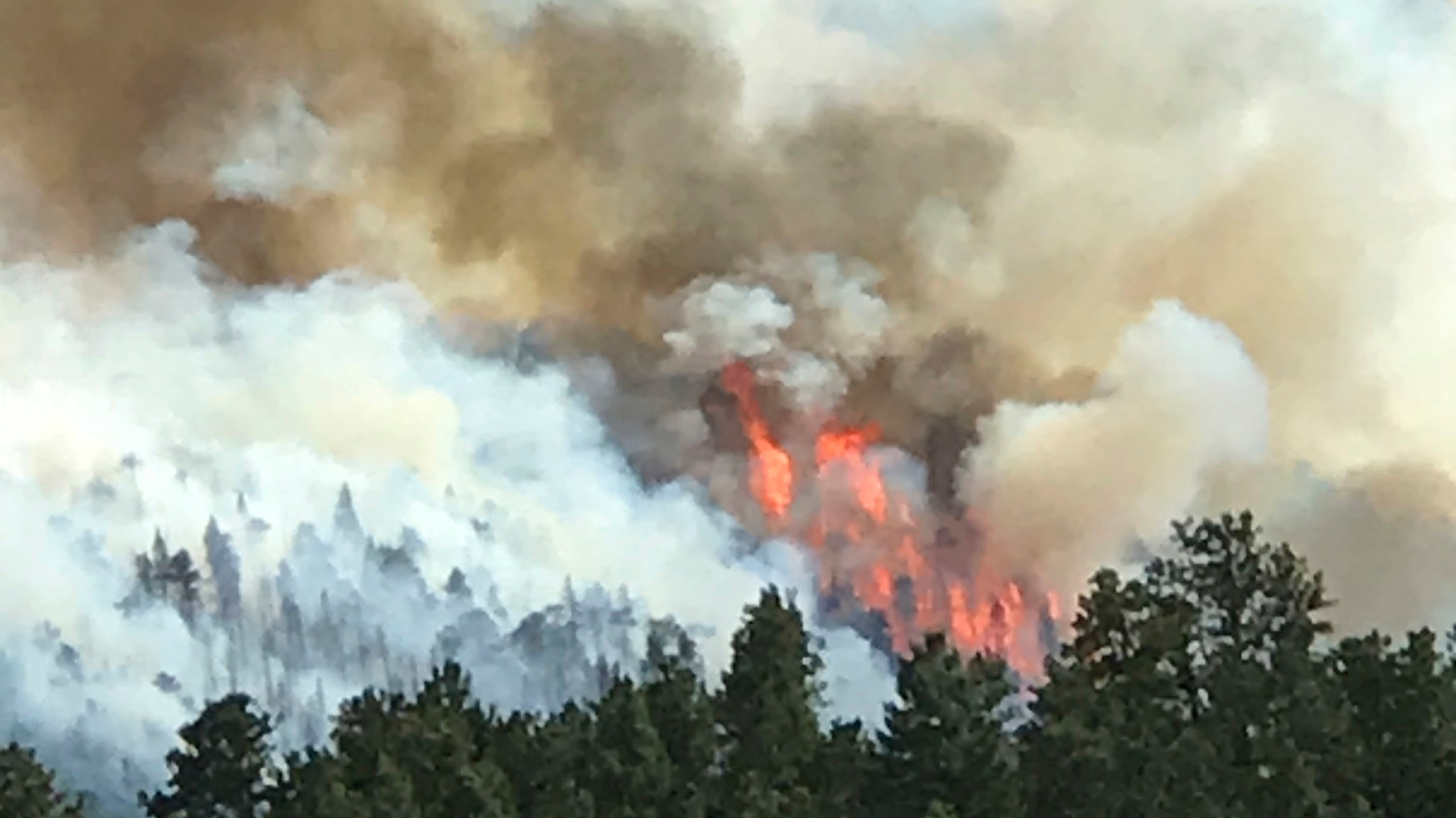In this photo provided by Robert Brown, a wildfire burns west of Evergreen, Colo., Monday, July 13, 2020. (Robert Brown via AP)