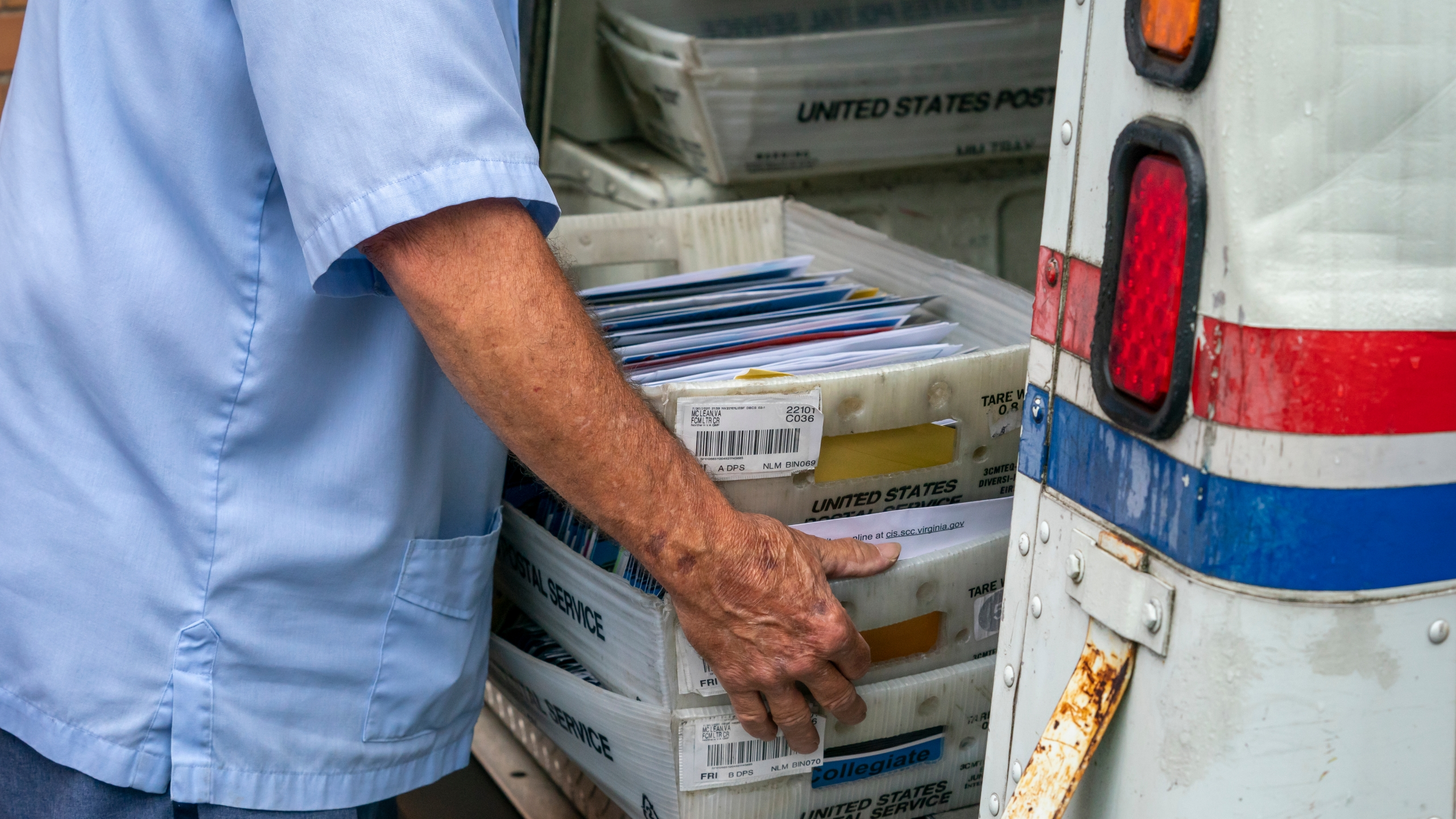 FILE - In this July 31, 2020, file photo, letter carriers load mail trucks for deliveries at a U.S. Postal Service facility in McLean, Va. (AP Photo/J. Scott Applewhite, File)