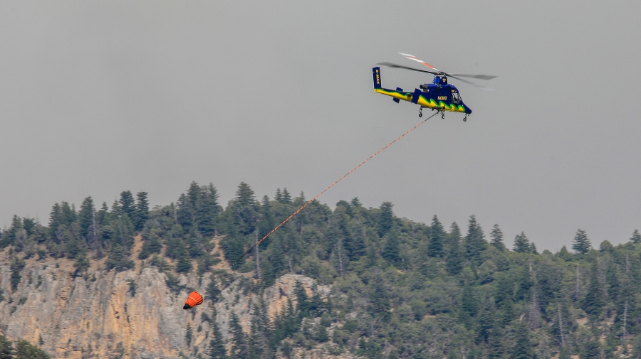 Helicopters fill with water from the Colorado River to fight the Grizzly Creek fire Sunday, Aug. 16, 2020, near Glenwood Springs, Colo. (Chris Dillmann/Vail Daily via AP)