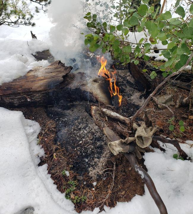 A log burning in the Cameron Peak Fire after the snowfall in September. / Courtesy Cameron Peak Fire Information