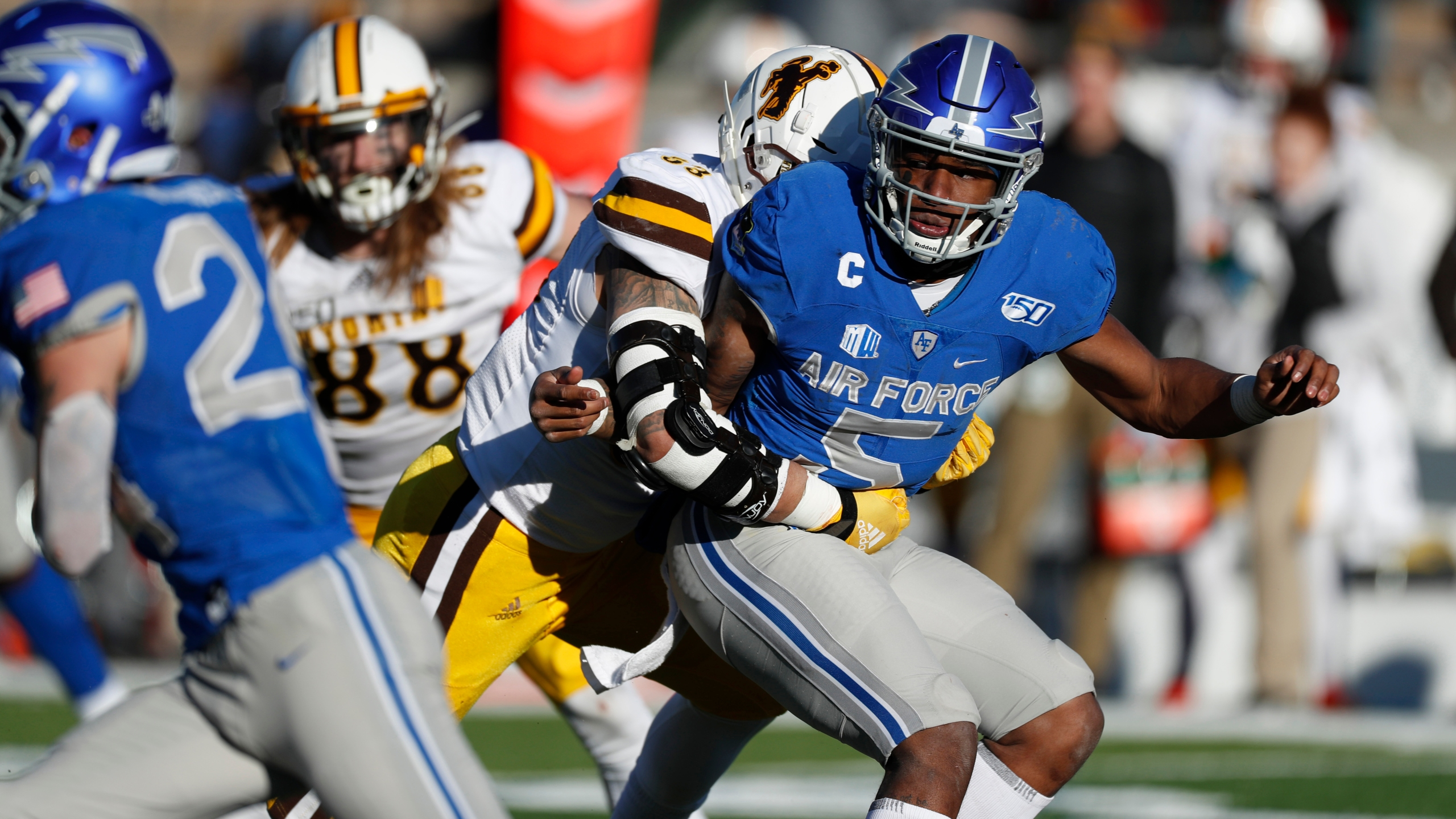 Wyoming defensive end Josiah Hall (53) hits Air Force quarterback Donald Hammond III (5) in the second half of an NCAA college football game Saturday, Nov. 30, 2019, at Air Force Academy, Colo. Air Force won 20-6. (AP Photo/David Zalubowski)