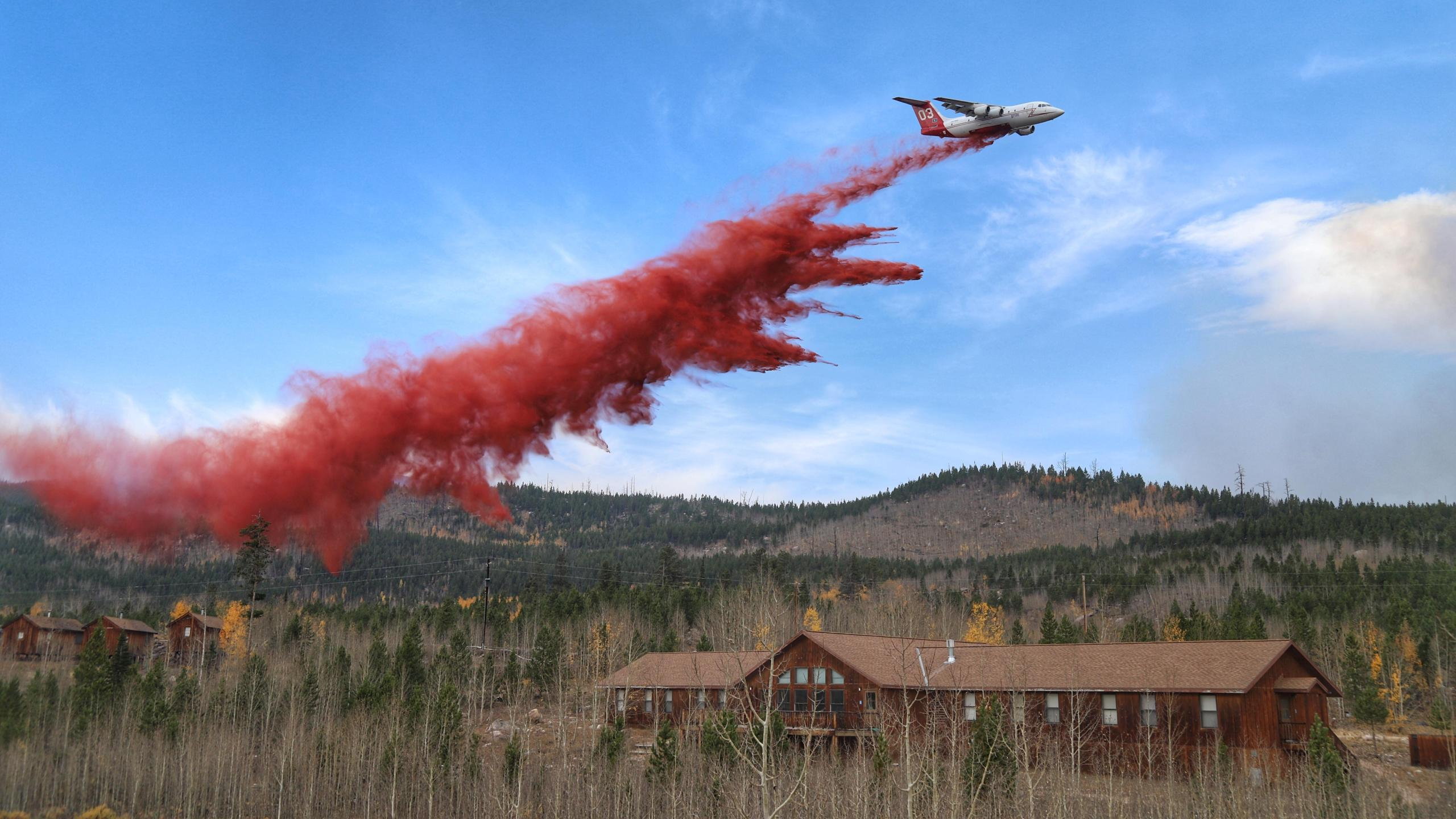 A BAe-146 large air tanker drops fire retandant behind buildings on the Colorado State University Mountain Campus in an effort to protect them from the Cameron Peak Fire Saturday, October 10. / Credit: Cameron Peak Fire, photo by NM Engine 964 Crew