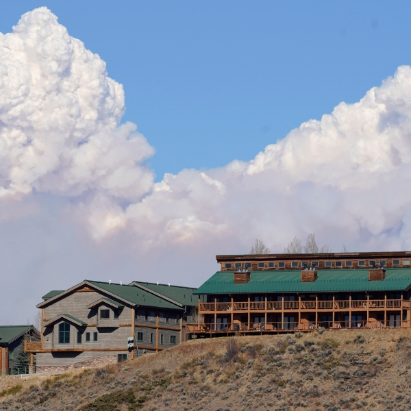Smoke rises from mountain ridges over homes as a wildfire burns Thursday, Oct. 22, 2020, in this view from Fraser, Colo. (AP Photo/David Zalubowski)