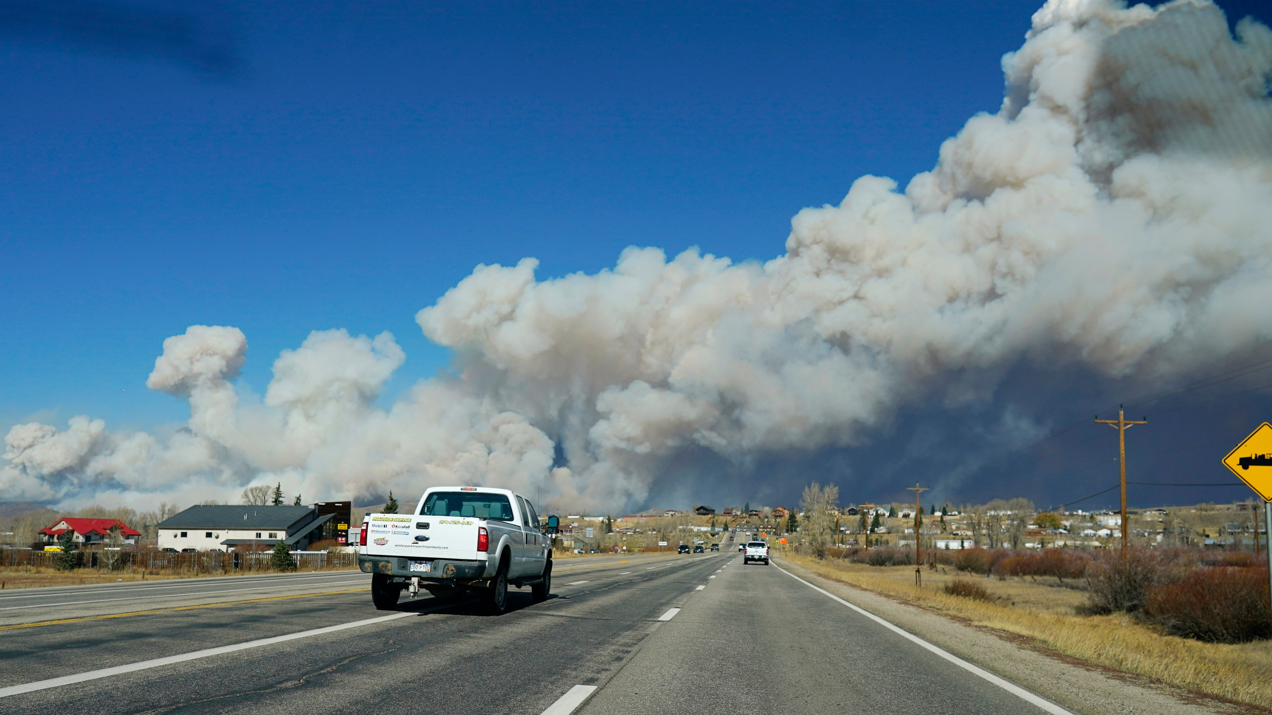 Smoke rises from mountain ridges as a wildfire burns while motorists head westbound along Highway 34 Thursday, Oct. 22, 2020, near Granby, Colo. (AP Photo/David Zalubowski)
