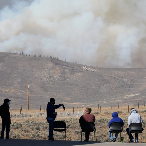 Smoke rises from mountain ridges as a wildfire burns while residents sit and watch Thursday, Oct. 22, 2020, near Granby, Colo. (AP Photo/David Zalubowski)