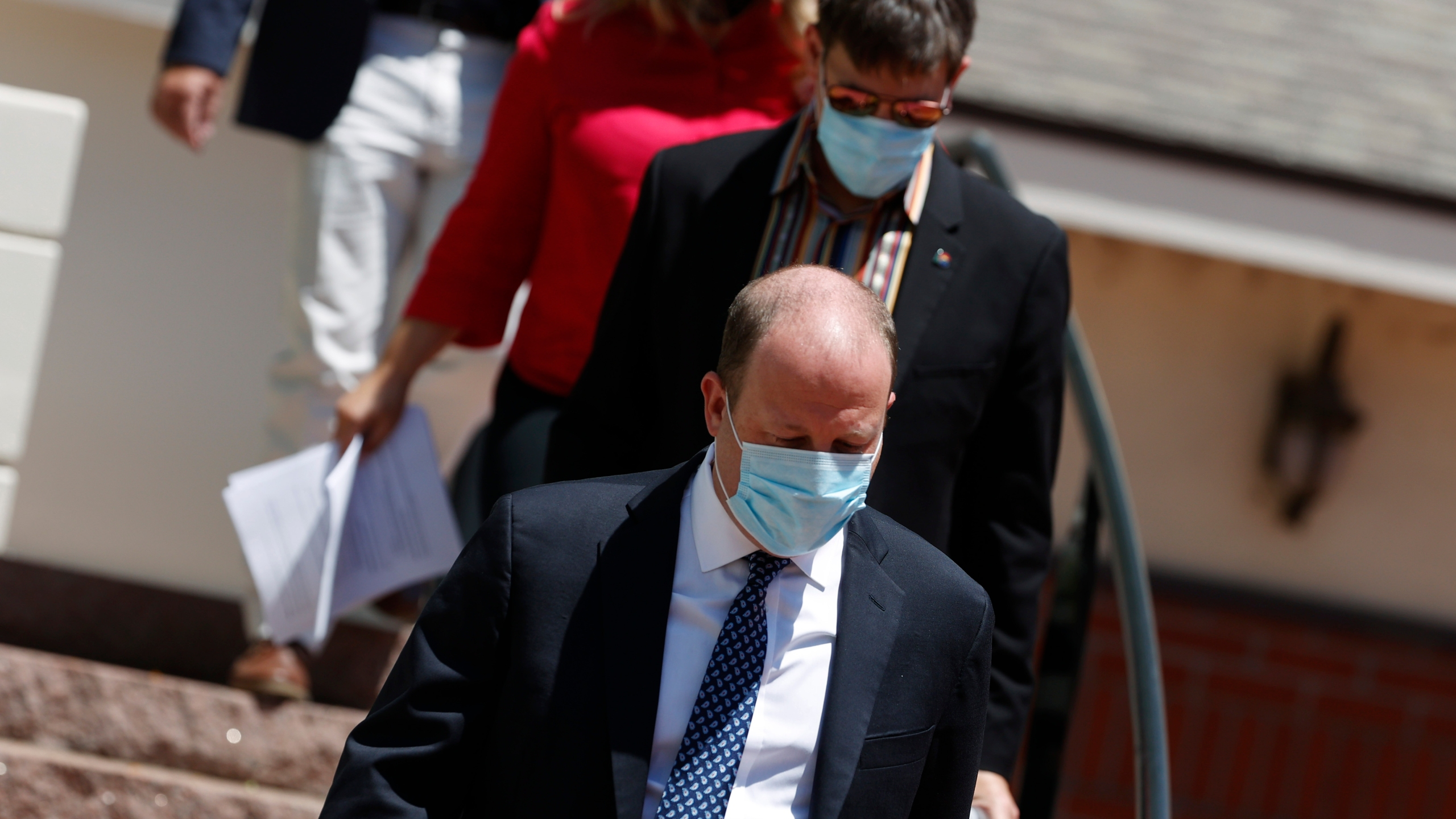 Colorado Gov. Jared Polis, front, navigates a set of stairs as he heads into a news conference with his partner, Marlon Reis, about the state's efforts to cut the spread of the new coronavirus Tuesday, June 30, 2020, in Denver. (AP Photo/David Zalubowski)