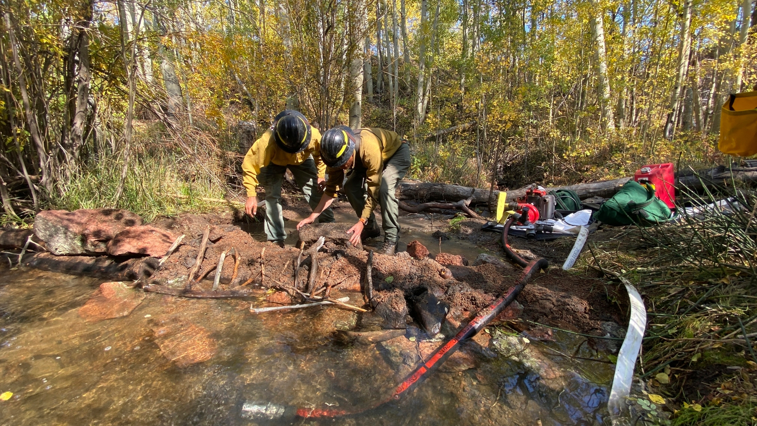 This Wednesday, Sept. 30, 2020, photo released by the U.S. Forest Service shows Little Laramie Engine crew members daming a stream for structure protection from the Mullen Fire in Foxpark, Wyo. (Lori Iverson/Rocky Mountain Blue Team/U.S. Forest Service via AP)