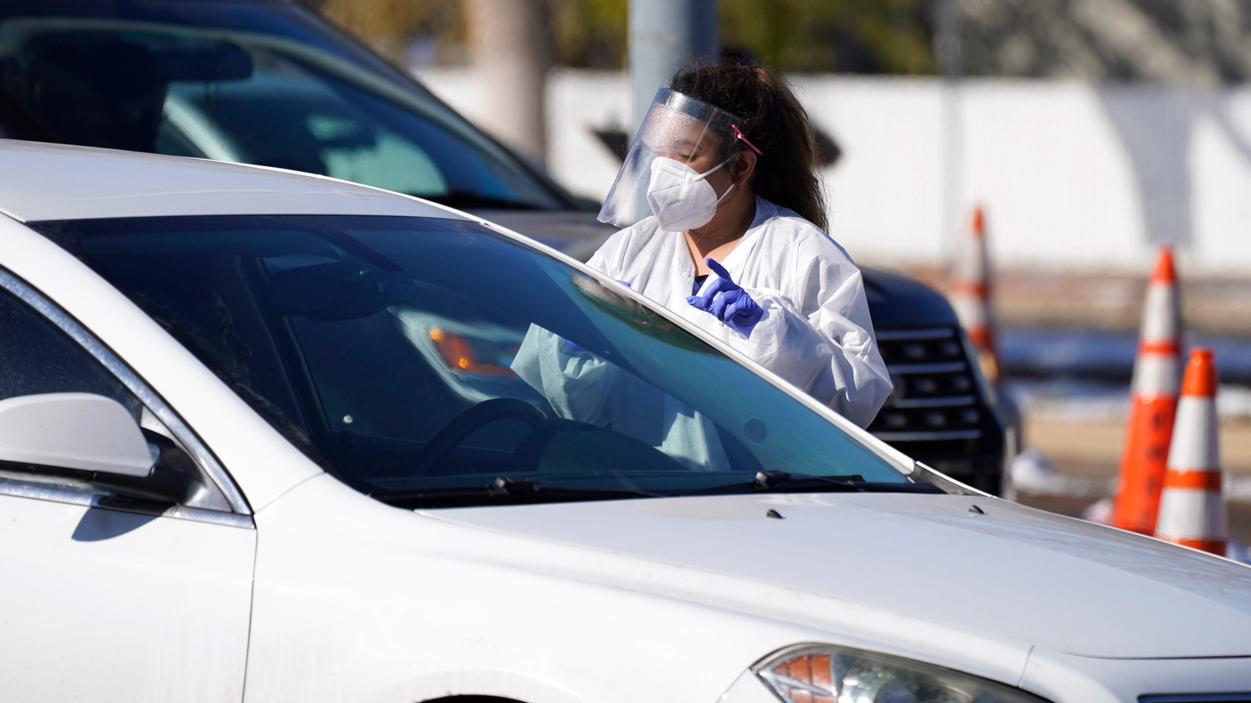 A tester talks to a motorist before administering a swab test at a drive-in, COVID-19 testing site Tuesday, Oct. 27, 2020, in Federal Heights, Colo.(AP Photo/David Zalubowski)