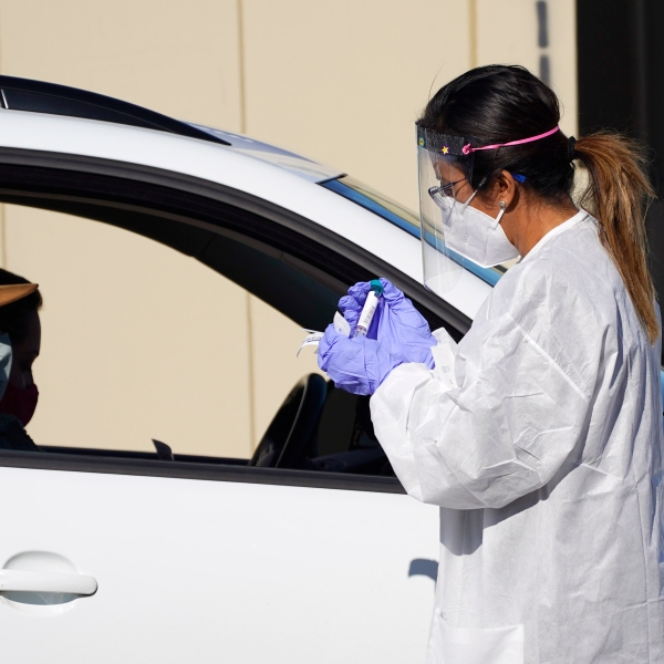 A tester prepares to administer a swab test at a drive-in COVID-19 testing site Tuesday, Oct. 27, 2020, in Federal Heights, Colo. (AP Photo/David Zalubowski)