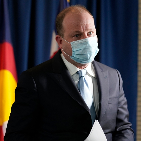 Colorado Governor Jared Polis wears a face mask as he leaves after a news conference about the state's response to the rapid increase in COVID-19 cases Tuesday, Nov. 24, 2020, in Denver. (AP Photo/David Zalubowski)