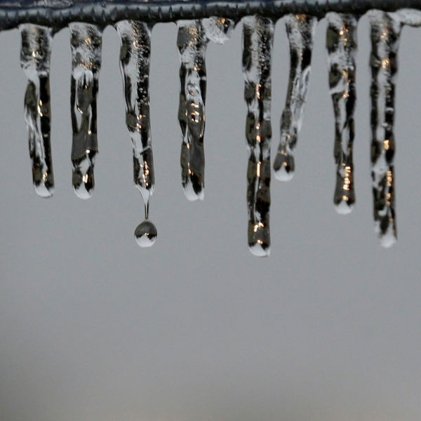 Ice hangs from a sign alongside an icy rural road Sunday, Jan. 18, 2015, near Newtown, Pa. (AP Photo/Mel Evans)