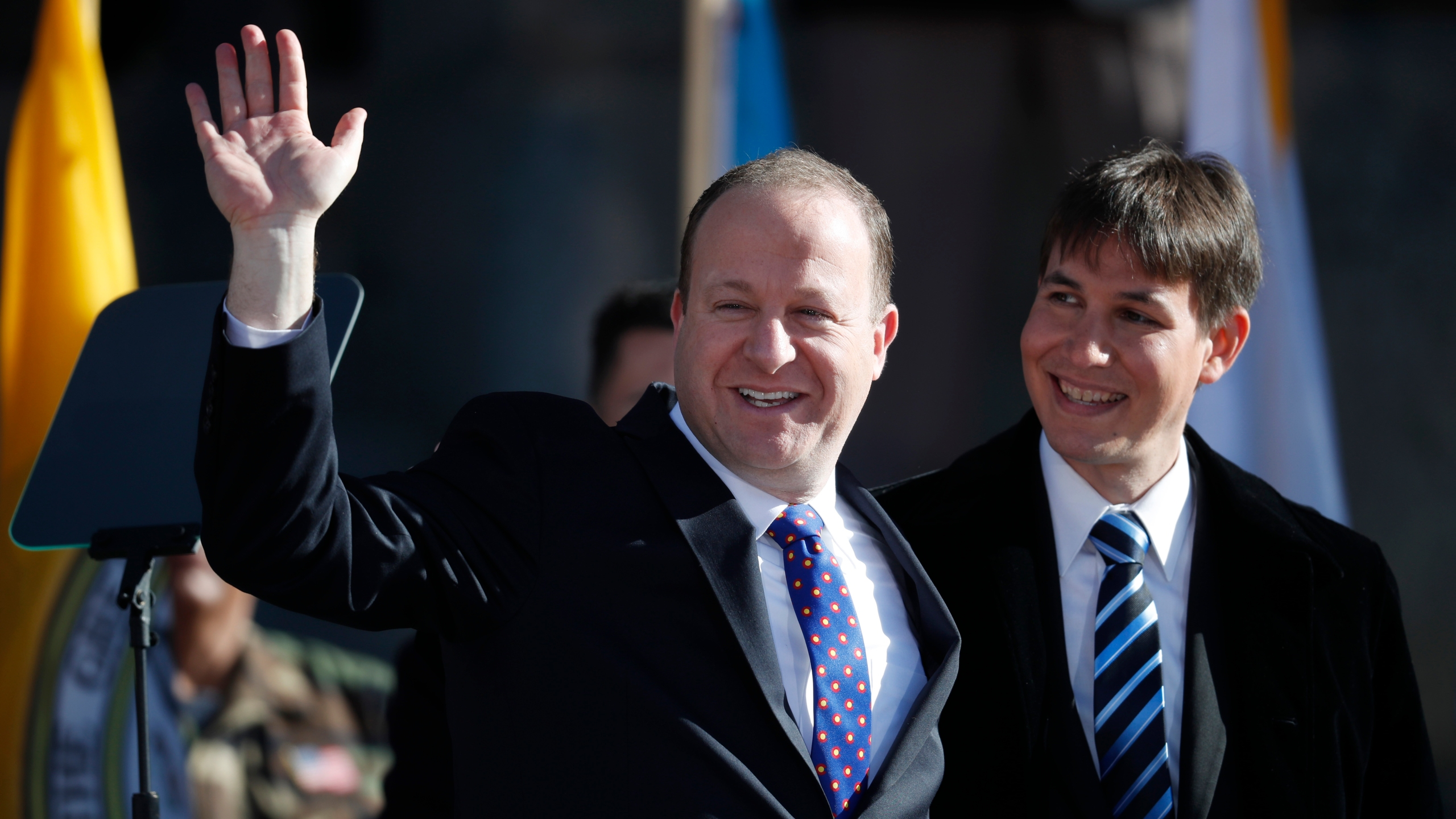 Colorado Gov. Jared Polis, left, waves to the crowd, accompanied by his partner, Marlon Reis, after Polis took the oath of office during his inauguration ceremony Tuesday, Jan. 8, 2019, in Denver. (AP Photo/David Zalubowski, Pool)