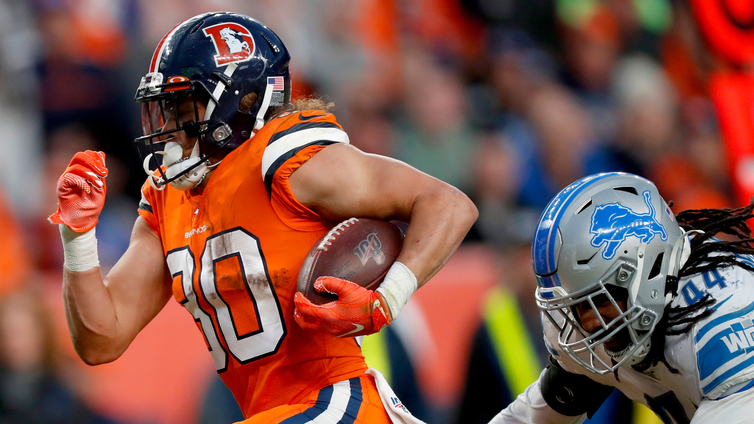 Denver Broncos running back Phillip Lindsay (30) breaks free from the grasp of Detroit Lions linebacker Jalen Reeves-Maybin (44) for a touchdown during the second half of an NFL football game, Sunday, Dec. 22, 2019, in Denver. (AP Photo/David Zalubowski)
