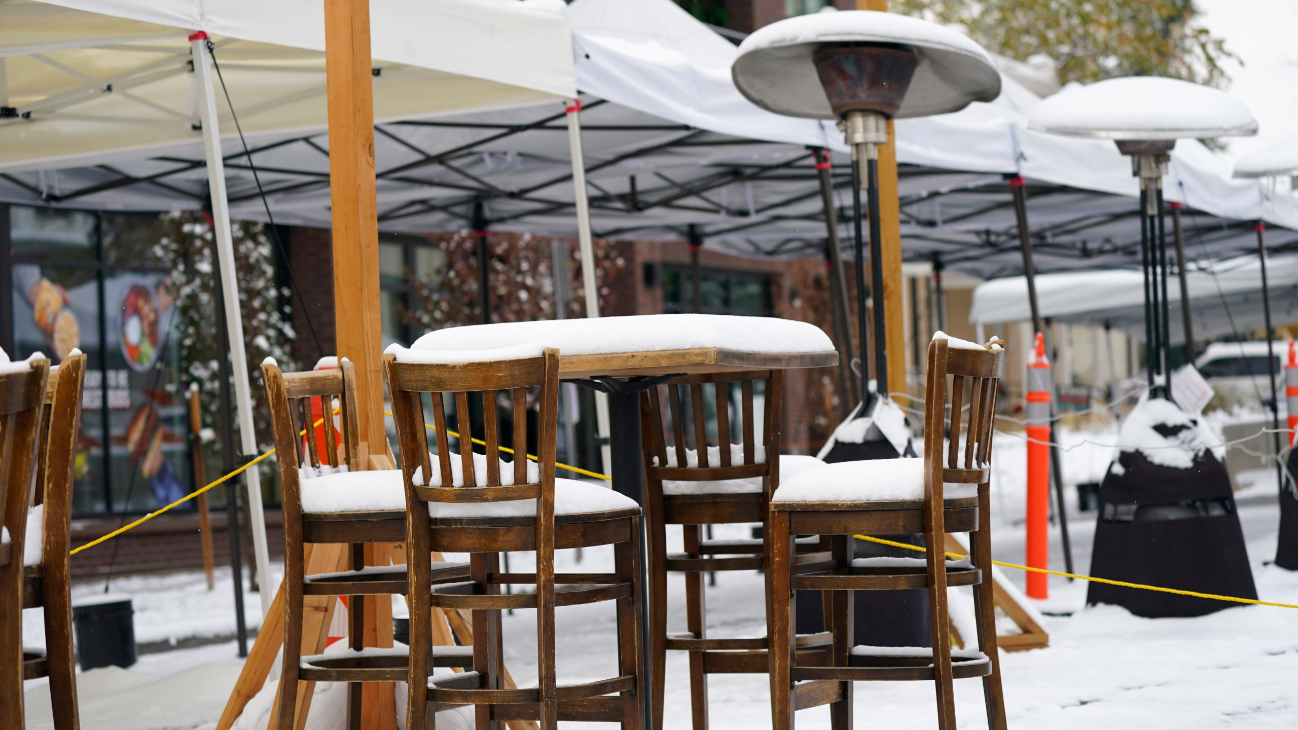 Outdoor seating set up to meet state COVID-19 protocols for bars is covered in snow ouitside a bar after an autumn storm swept over the intermountain West Monday, Oct. 26, 2020, in Denver. (AP Photo/David Zalubowski)
