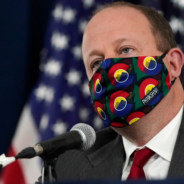 Colorado Governor Jared Polis makes a point about the state's modeling efforts against the coronavirus during a news conference Tuesday, March 16, 2021, in Denver. (AP Photo/David Zalubowski)