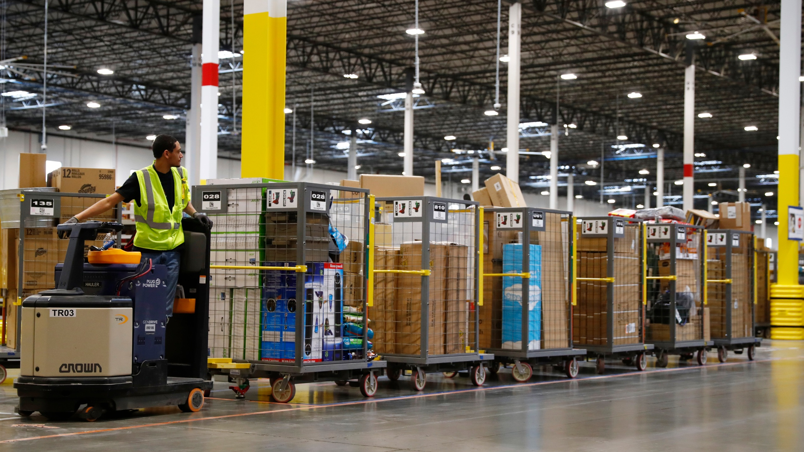 A worker checks the long line of carts that he is about to pull along in the Amazon fulfillment center Thursday, May 3, 2018, in Aurora, Colo. (AP Photo/David Zalubowski)