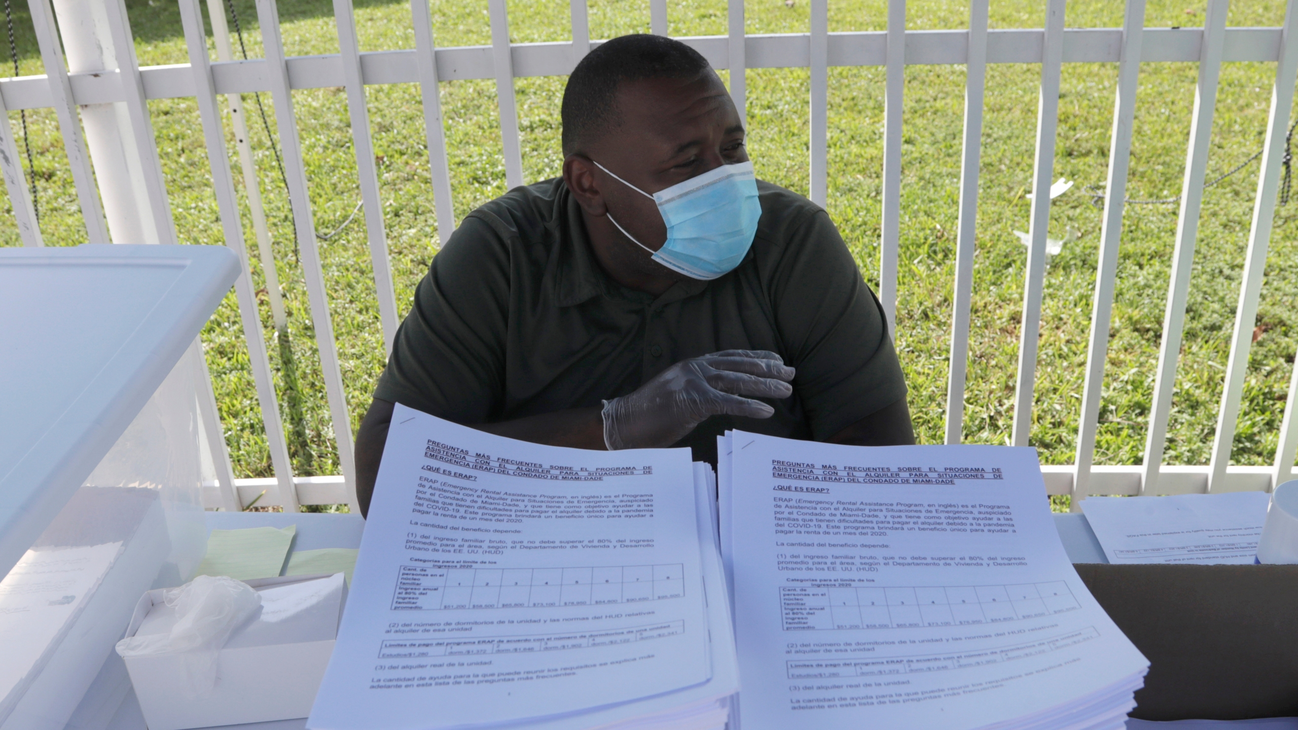 Tino Duncombe works at a drive-up site where applications in Spanish are offered for the Emergency Rental Assistance Program, a one-time benefit to help with one month's rent offered by Miami-Dade County, during the coronavirus pandemic, Thursday, July 16, 2020, in Miami. (AP Photo/Lynne Sladky)