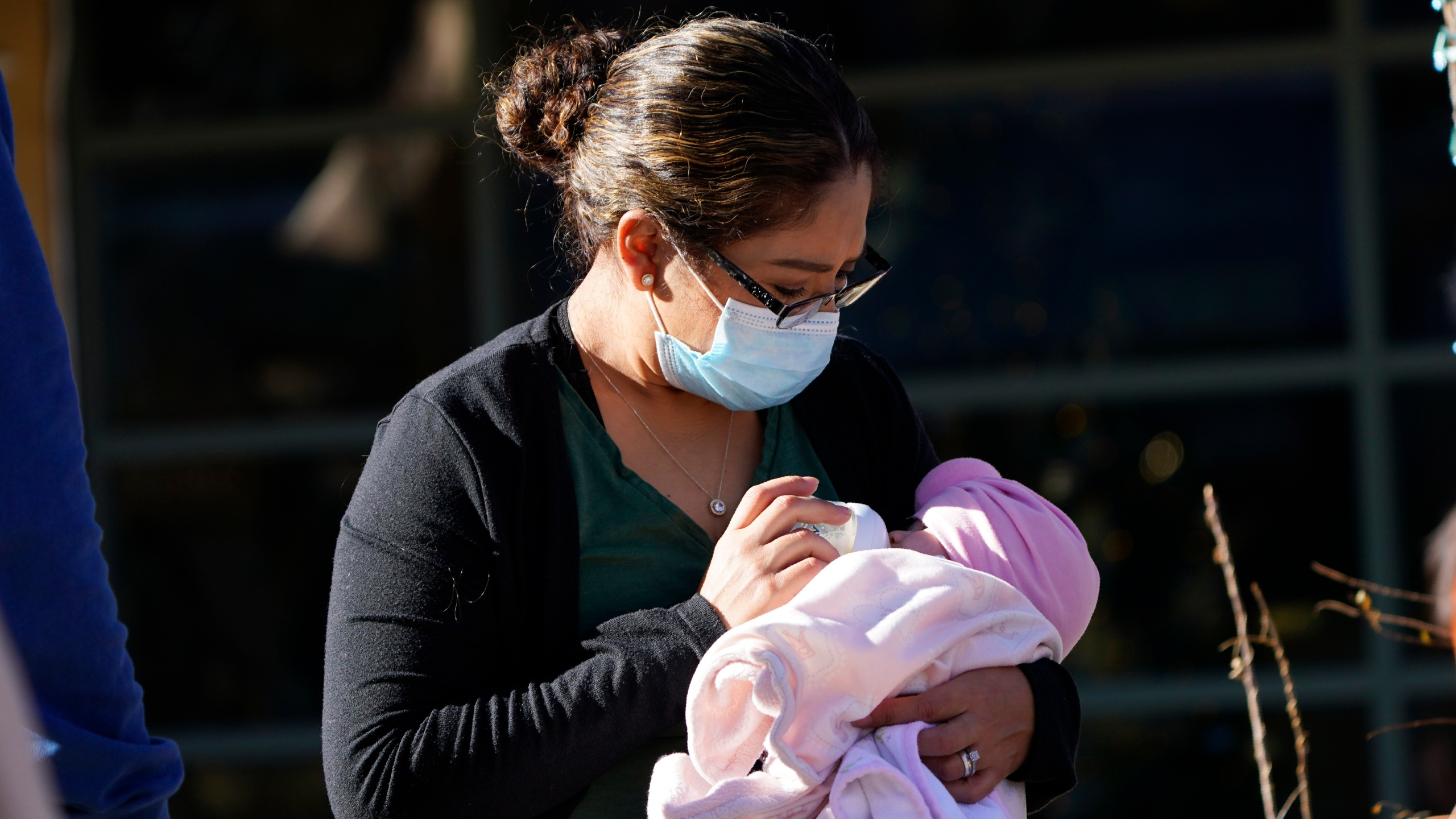 A woman feeds a baby while waiting for entry at the Denver Zoo Monday, Dec. 7, 2020, in east Denver. (AP Photo/David Zalubowski)