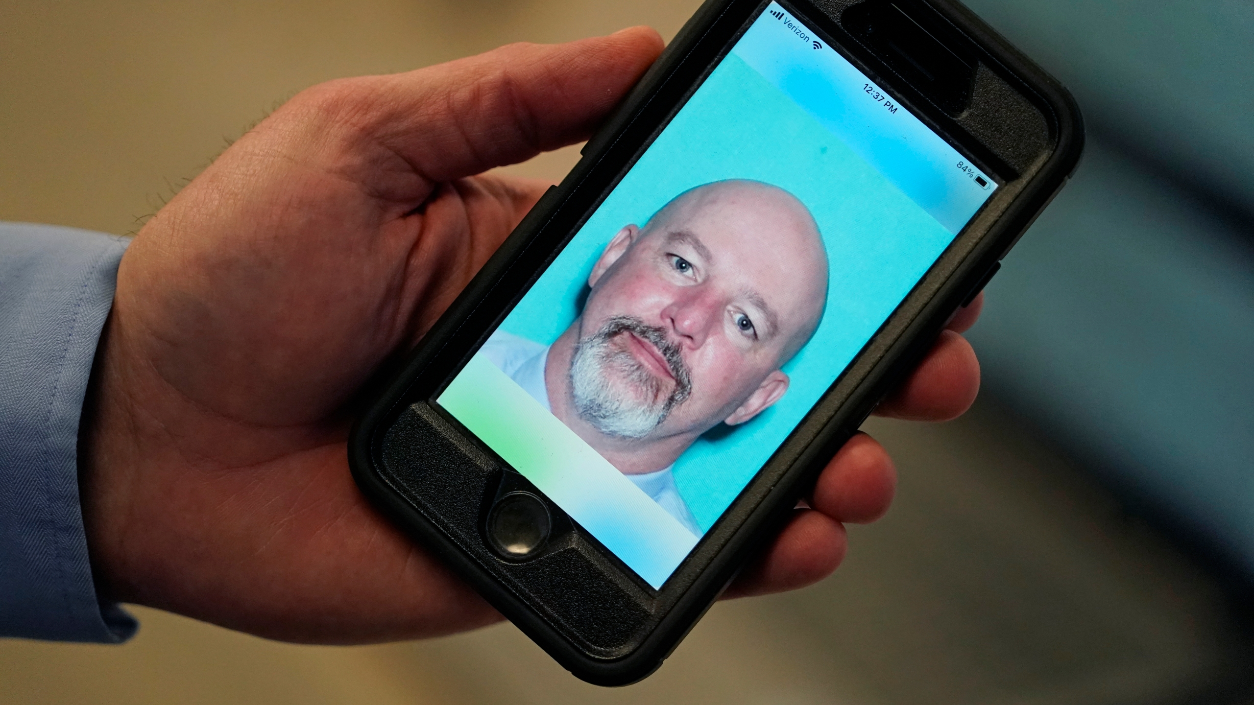 Ryan Williams, with the Utah Drivers License Division, holds his cell phone with the pilot version of the state's mobile ID on Wednesday, May 5, 2021, in West Valley City, Utah. (AP Photo/Rick Bowmer)