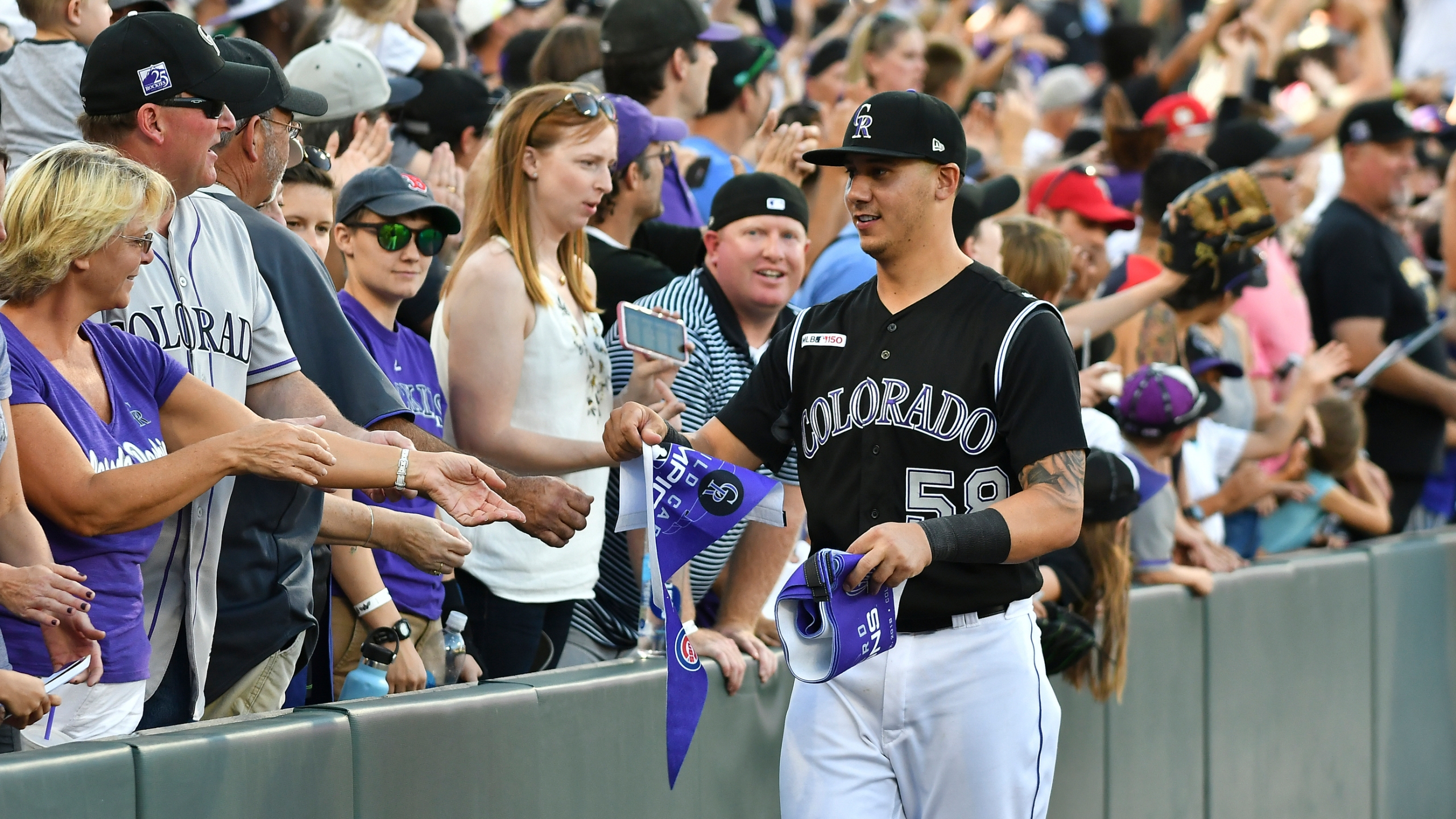 Colorado Rockies catcher Dom Nunez (58) hands out souvenirs to the fans after their win over the Milwaukee Brewers 4-3 in 13 innings at a baseball game Sunday, Sept. 29, 2019, in Denver. (AP Photo/John Leyba)