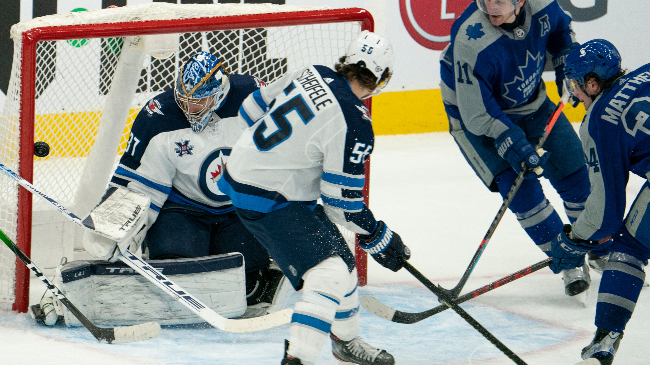 Toronto Maple Leafs center Auston Matthews(34) gets his second goal of the game on Winnipeg Jets goaltender Connor Hellebuyck(37) during an NHL hockey game, Tuesday, March 9, 2021, in Toronto, Canada. (AP Photo/Peter Power)