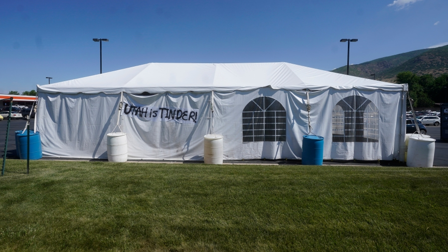 """A """"UTAH is TINDER"""" sign is placed on the side of a fireworks vendor tent Friday, June 25, 2021, in Centerville, Utah. (AP Photo/Rick Bowmer)"""